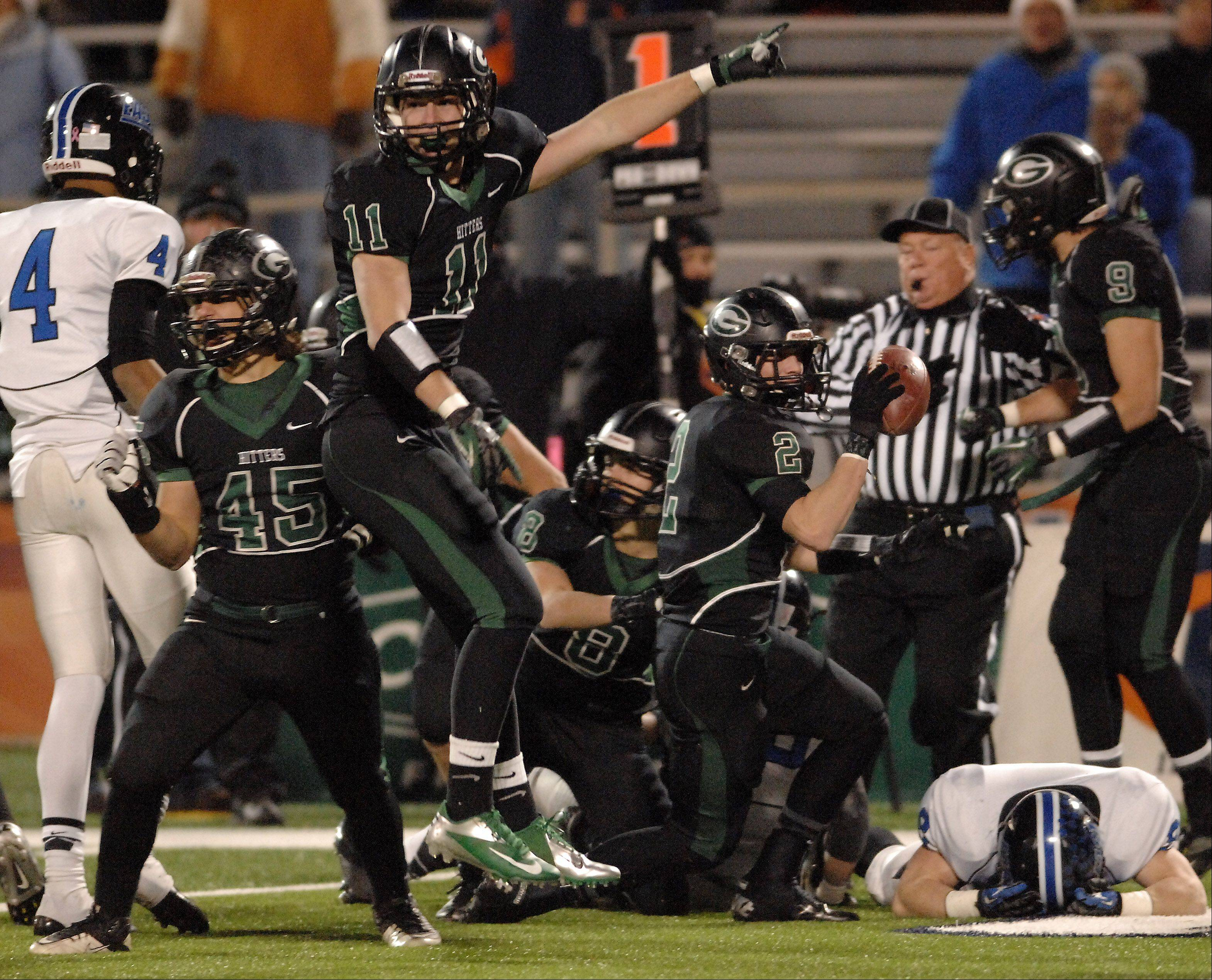 Glenbard West players, including Jordan Hassan, 45, and Grant Greeno, 11, celebrate as Joe Marconi, 2, comes up with a fumble recovery during Saturday's Class 7A state title game at Memorial Stadium in Champaign.