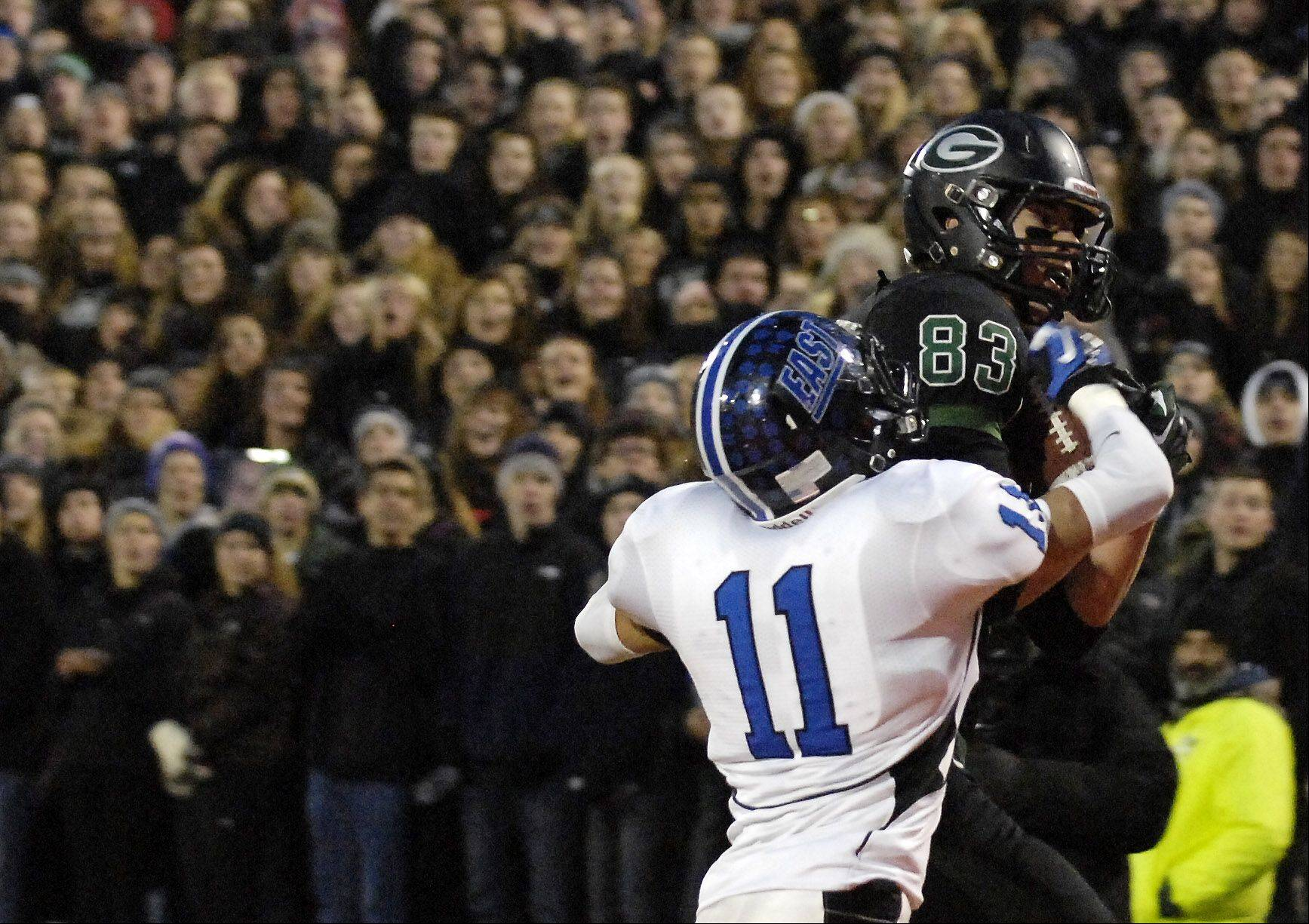 Glenbard West's Nathan Marcusm 83, hauls in a first-half touchdown catch in front of Lincoln-Way East's Moe Almasri during Saturday's Class 7A state title game at Memorial Stadium in Champaign.