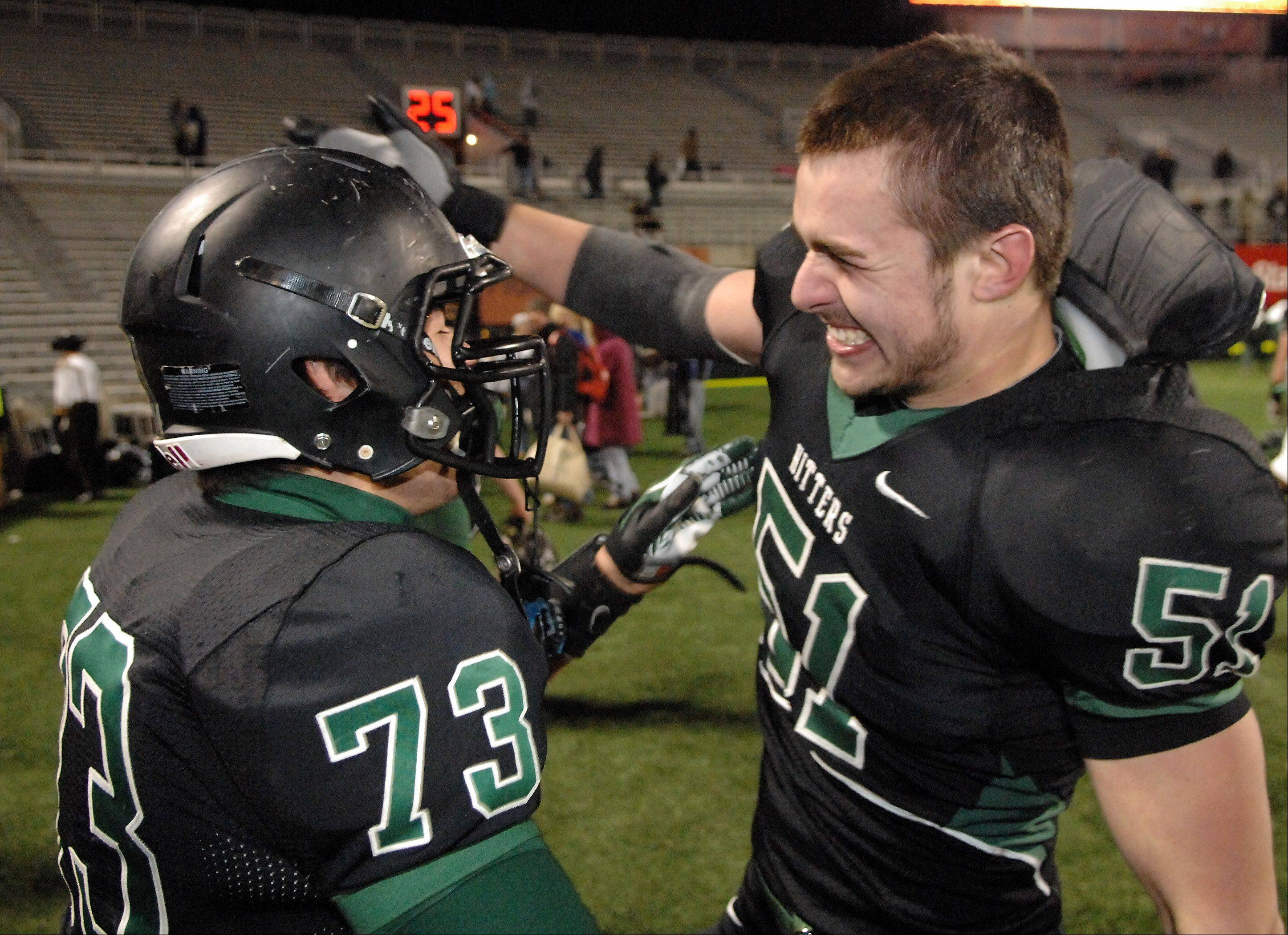 Glenbard West's Nick Garland, 51, grabs teammate Alex Morreale, 73, after winning the Class 7A state title game at Memorial Stadium in Champaign Saturday.