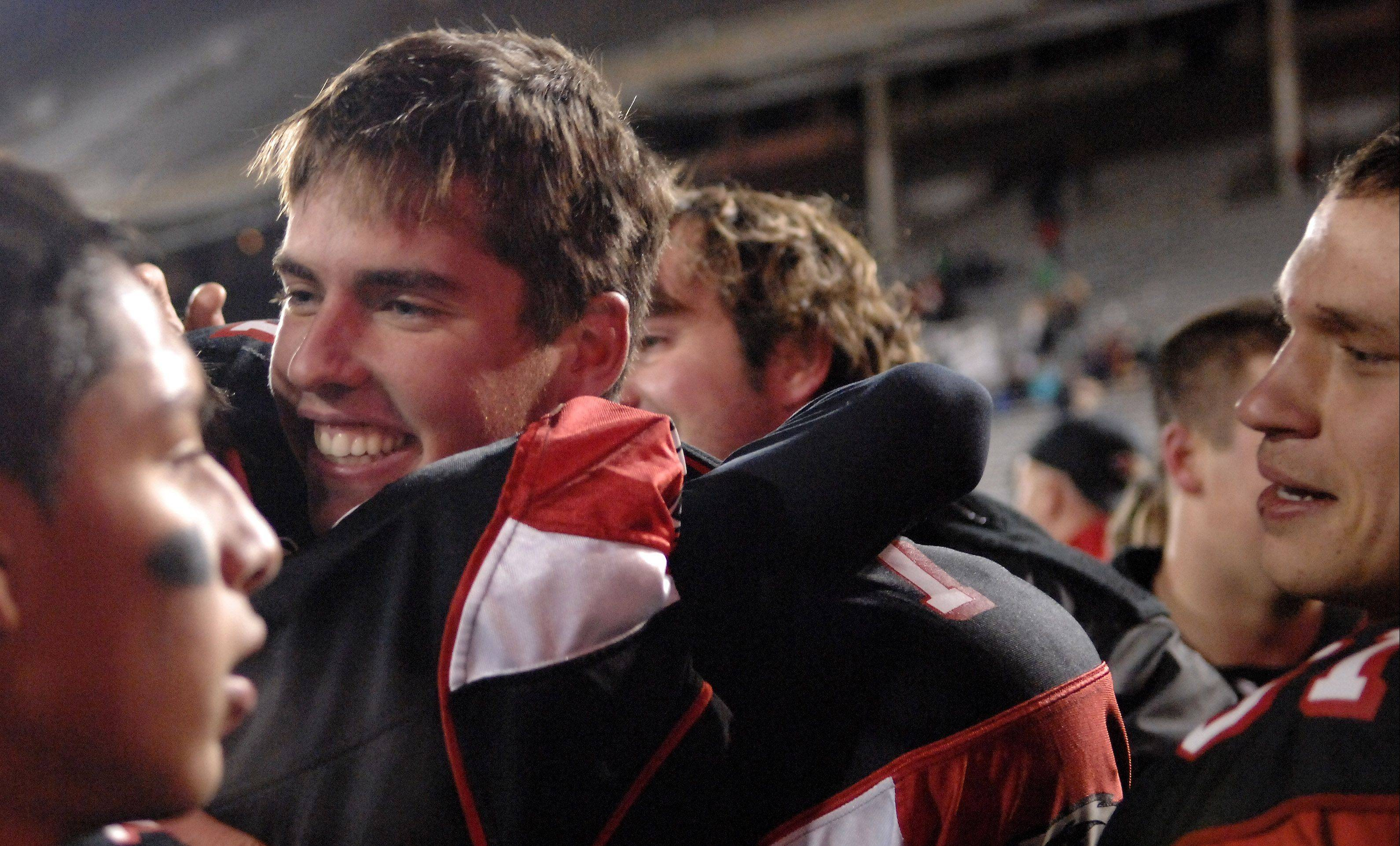 Aurora Christian quarterback Ryan McQuade hugs a teammate following their win over Tolono Unity Friday in Champaign.