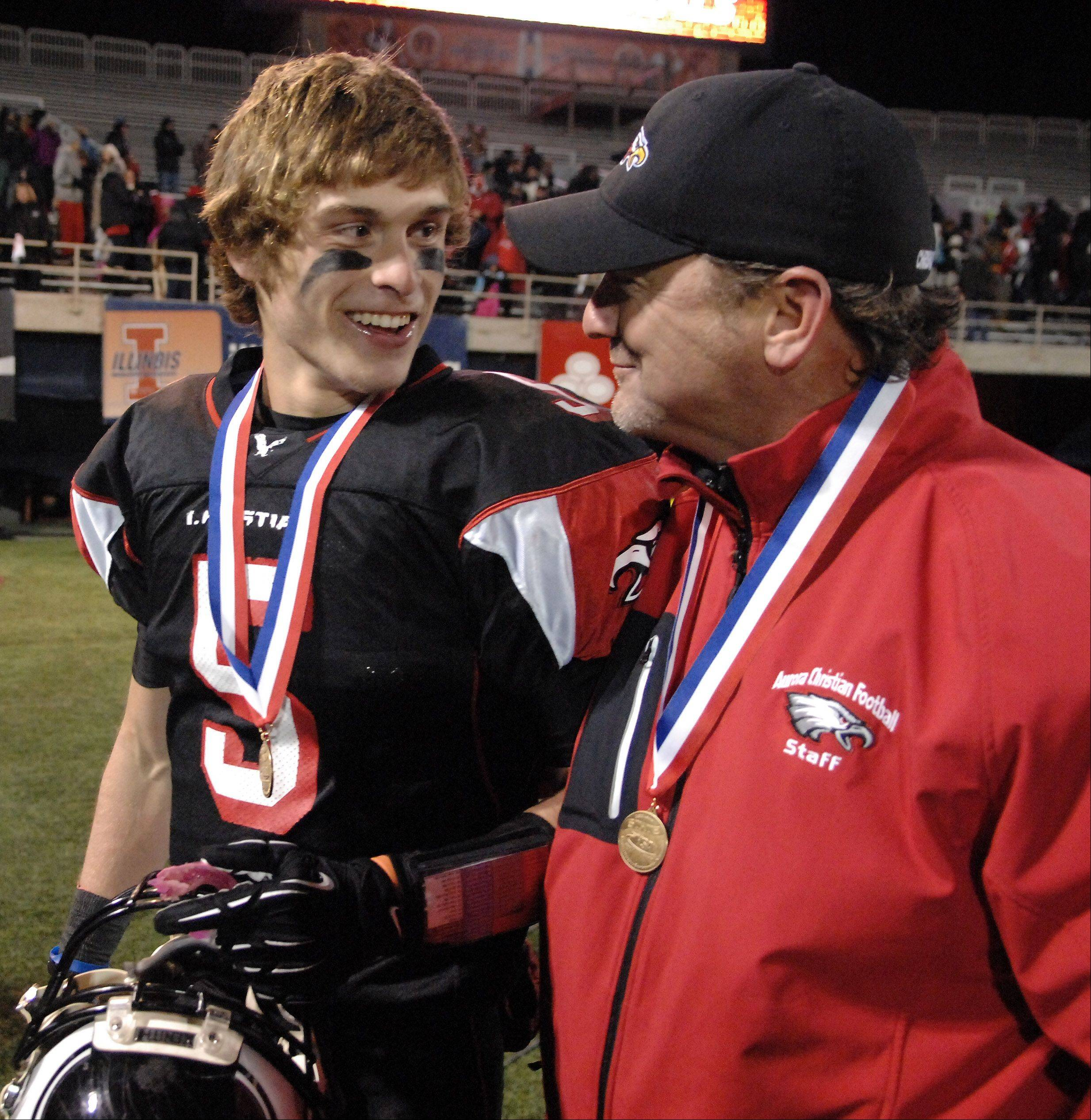Rick West/rwest@dailyherald.com Aurora Christian's Noah Roberts and coach Don Beebe share a moment after the trophy presentation following their win over Tolono Unity during Friday's Class 3A state championship game at Memorial Stadium in Champaign.