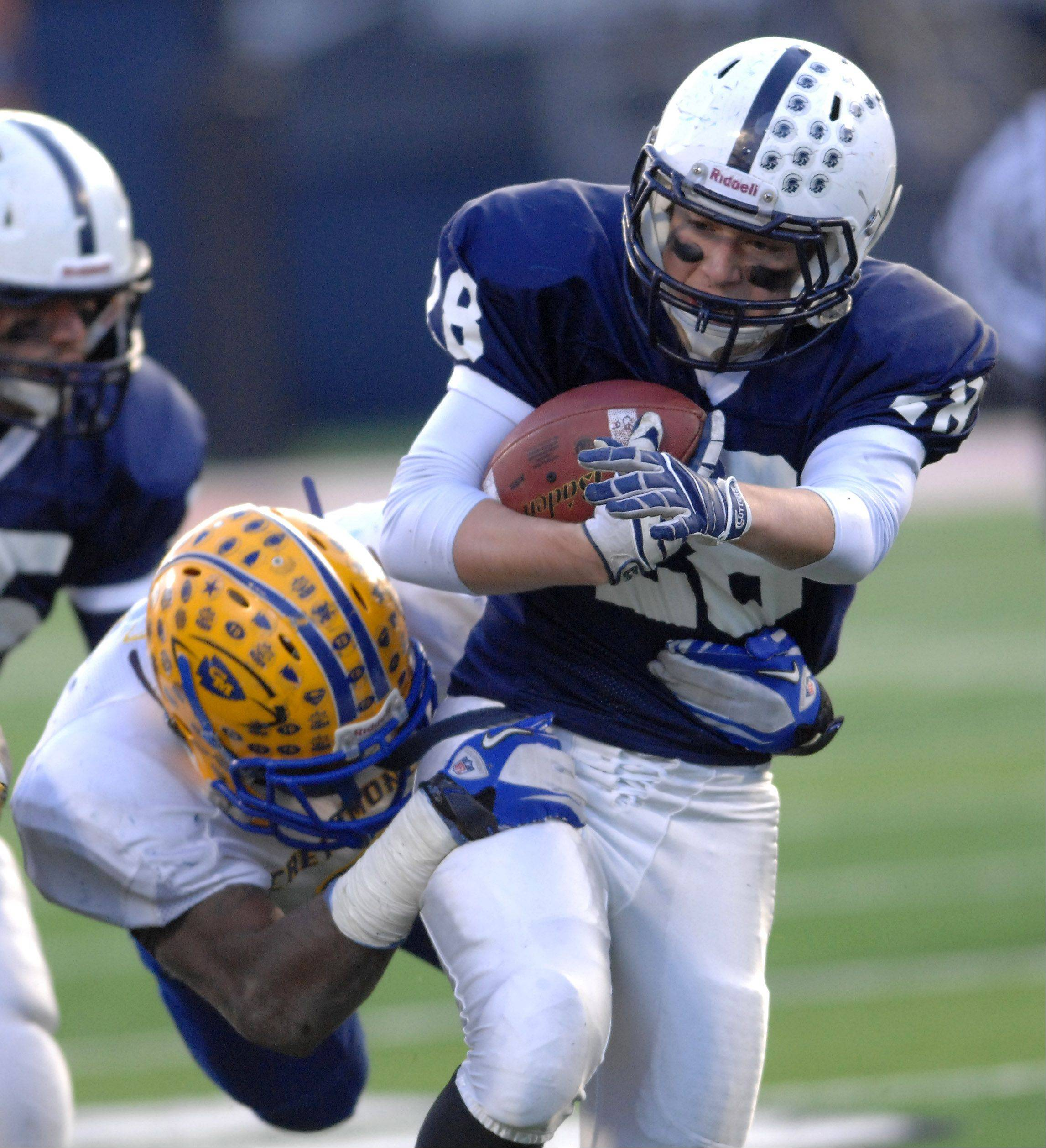 Cary-Grove's Joey Scott (28) breaks through a tackle during Saturday's Class 6A state title game at Memorial Stadium in Champaign.