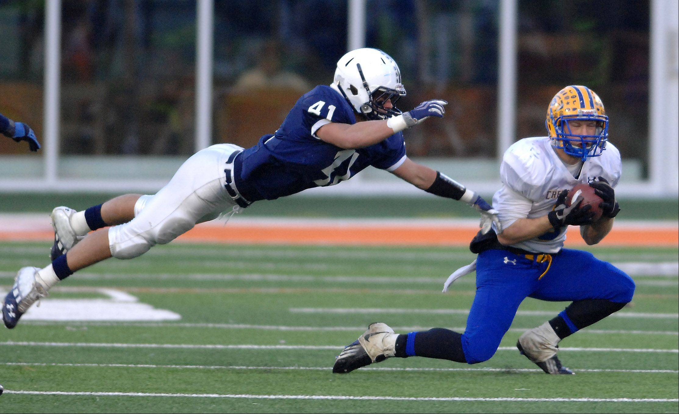 Cary-Grove's Zach Marszal (41) dives but can't break up a pass that is caught by a Crete-Monee receiver during Saturday's Class 6A state title game at Memorial Stadium in Champaign.