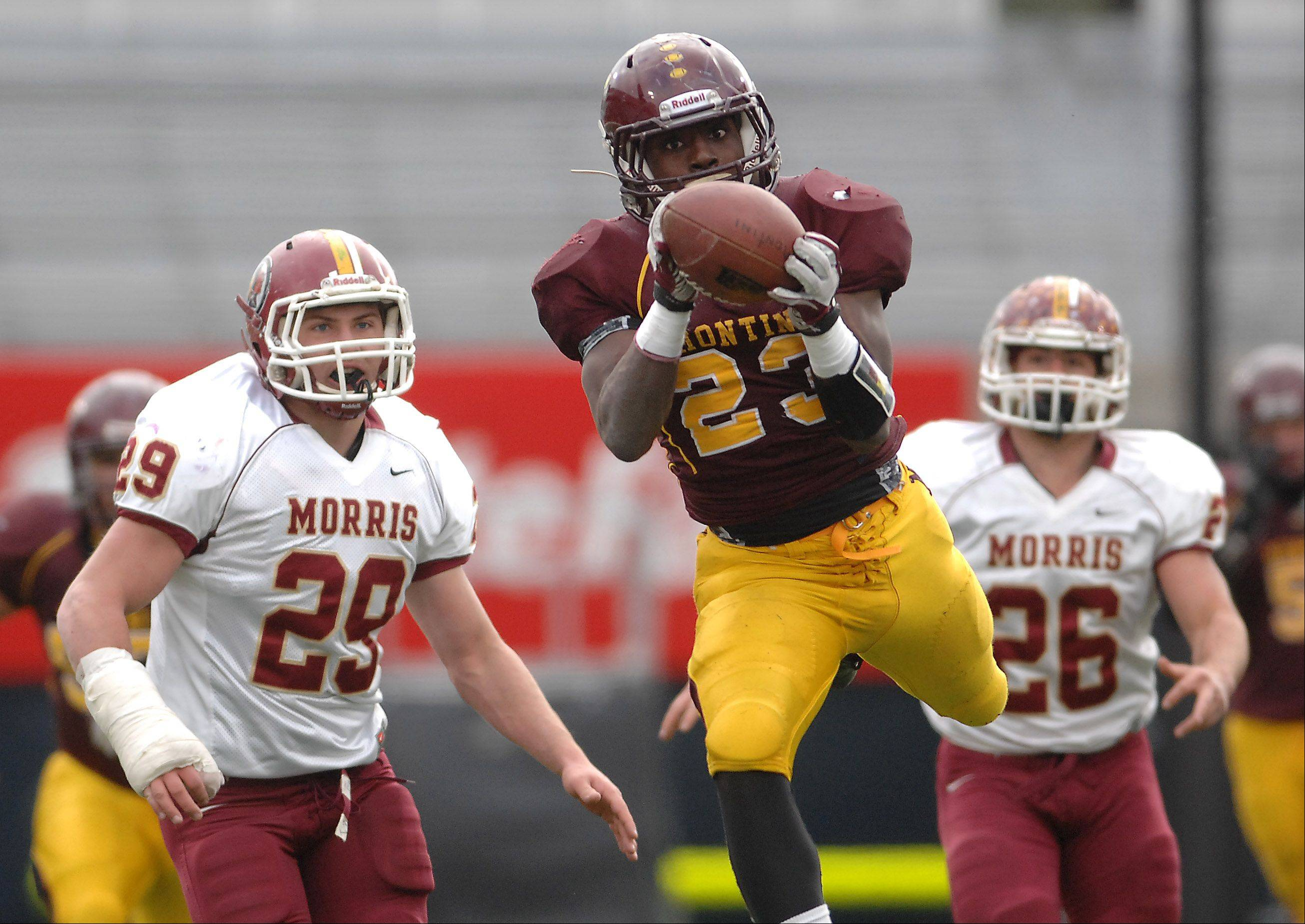 Montini's Dimitri Taylor (23) hauls in a pass that he turns into a second quarter touchdown after a run during Saturday's Class 5A state title game against Morris at Memorial Stadium in Champaign.