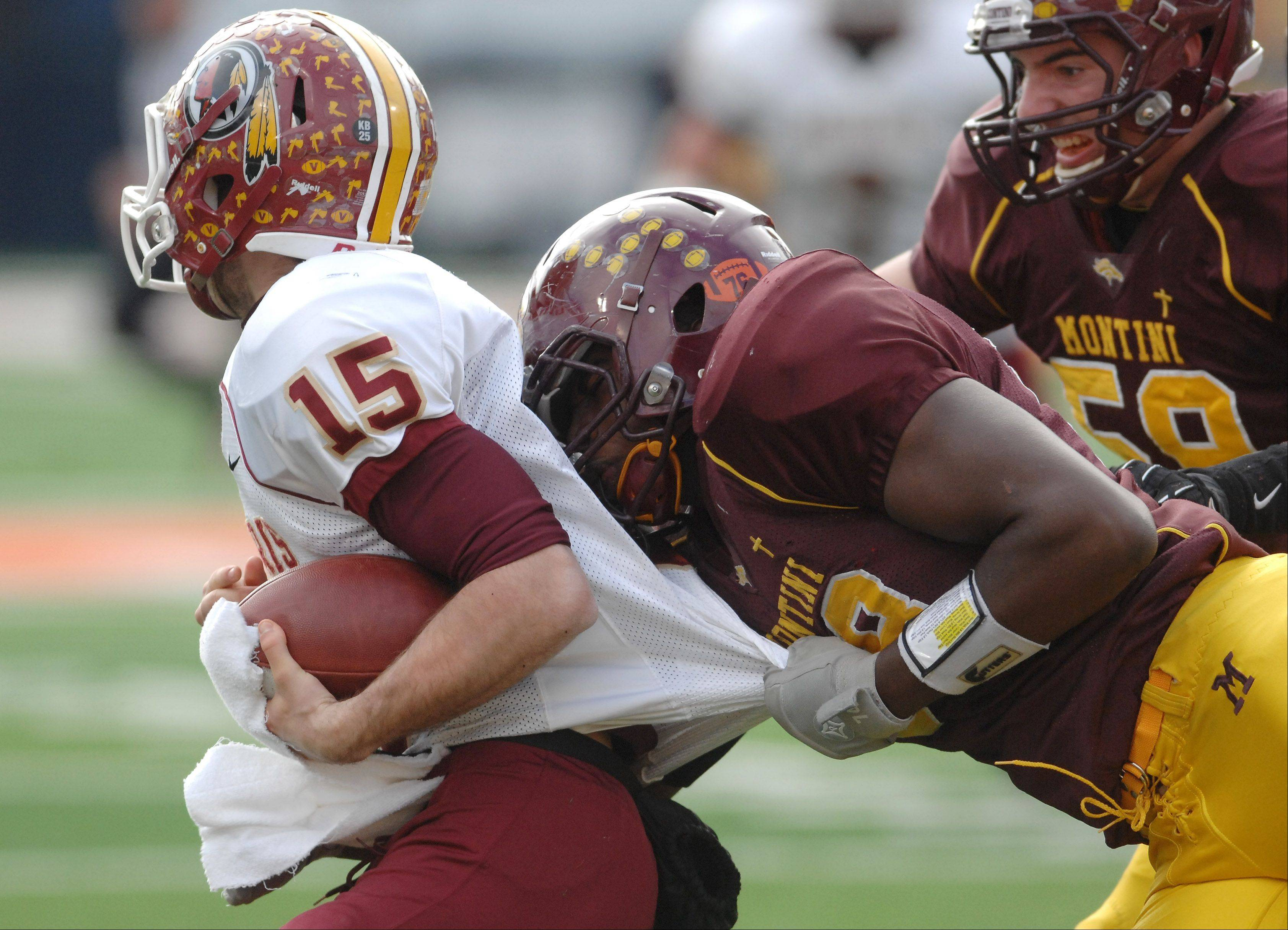 Montini's Fred Beaugard (58) and Dylan Thompson (59), right, combine on a sack of Morris quarterback Zach Cinnamon during Saturday's Class 5A state title game at Memorial Stadium in Champaign.