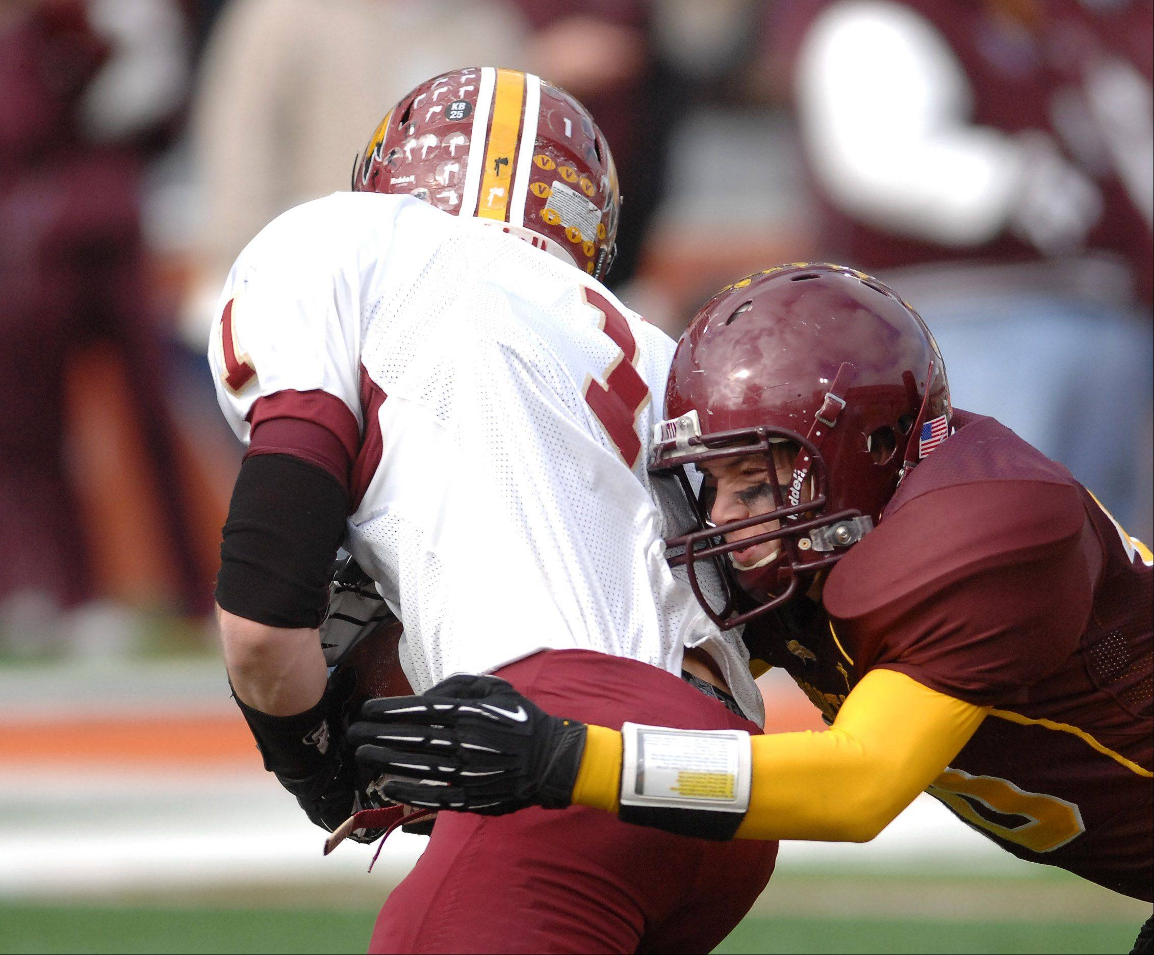 Montini's Tyler Quick (10) brings down Jake Hogan of Morris for a loss during Saturday's Class 5A state title game at Memorial Stadium in Champaign.