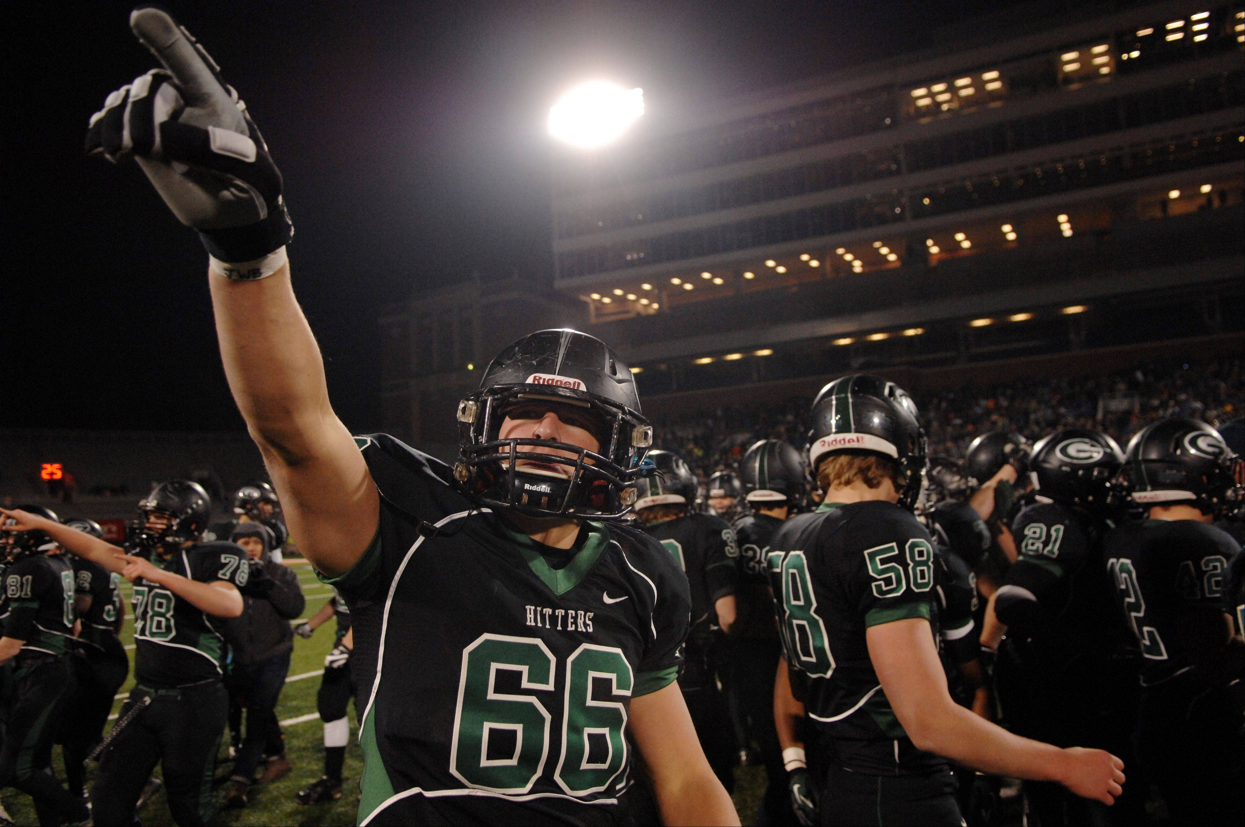 Glenbard West offensive linesman Max Bruere (66) salutes the crowd as he and the Hilltoppers celebrate their win over Lincoln-Way East during Saturday's Class 7A state title game at Memorial Stadium in Champaign.