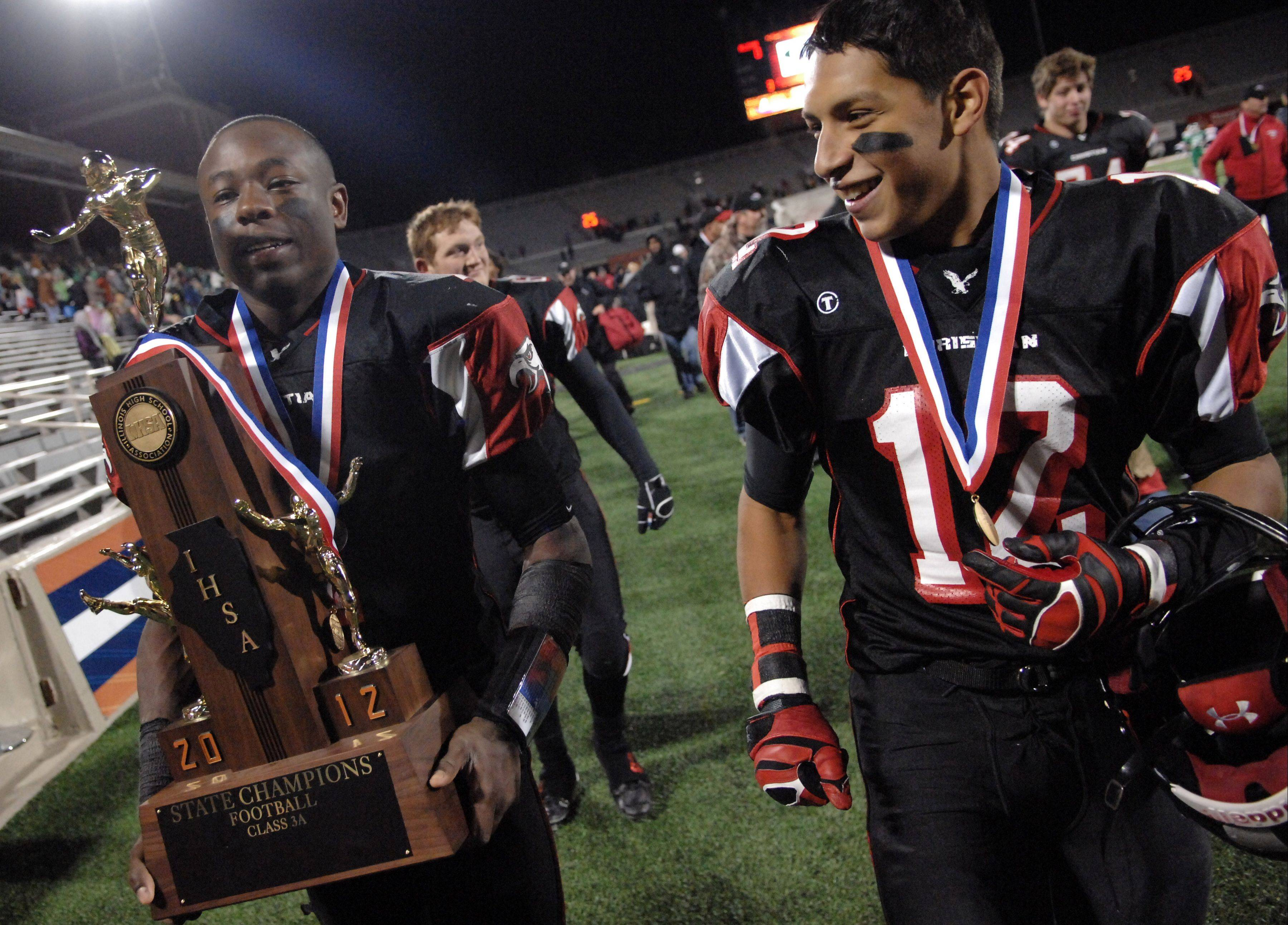 Brandon Mayes walks off the Memorial Stadium field carrying the second state trophy he helped the school win.