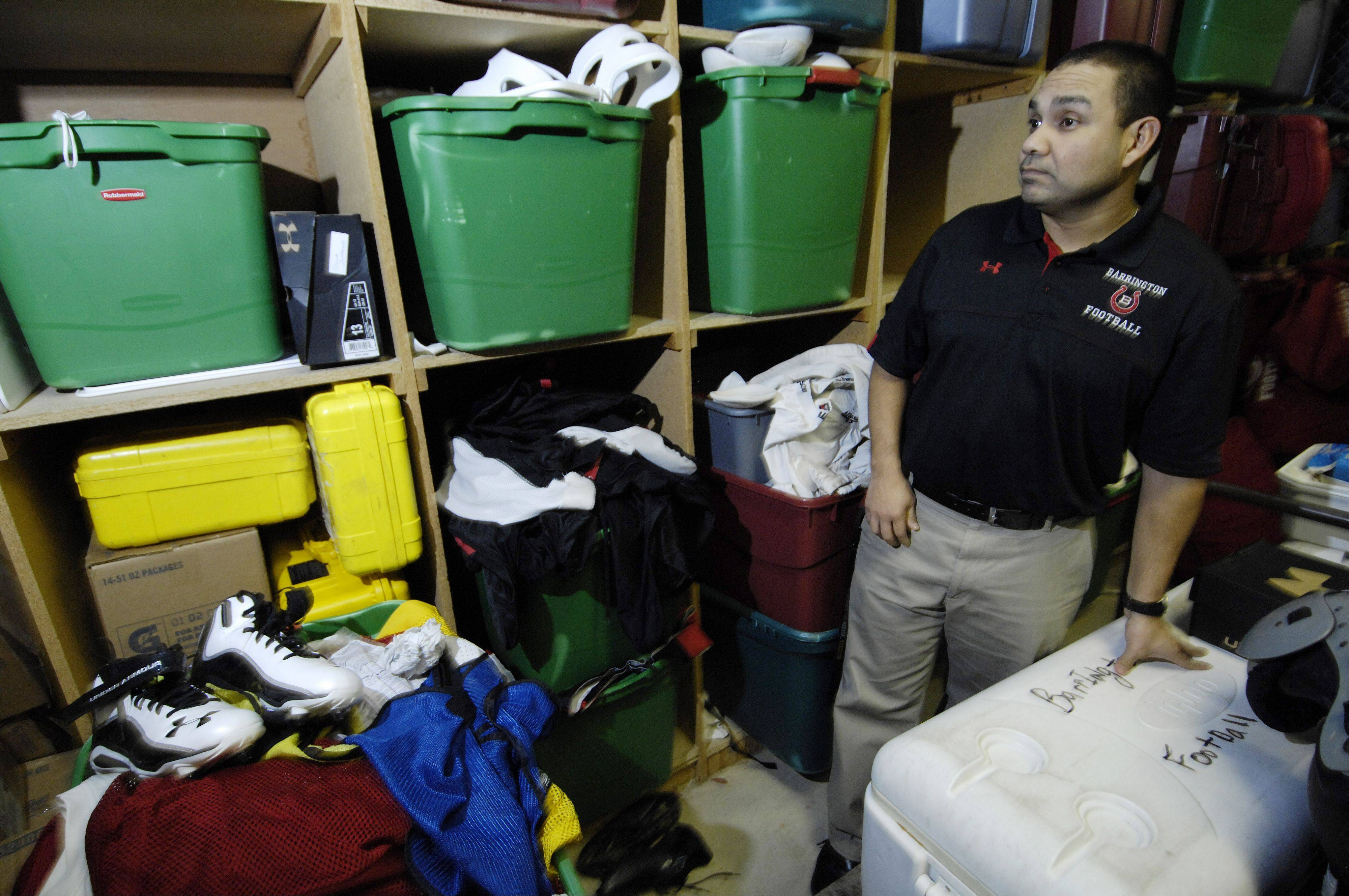 Barrington football coach Joe Sanchez in the equipment room, showing the types of football equipment that was donated to Kelvyn Park.