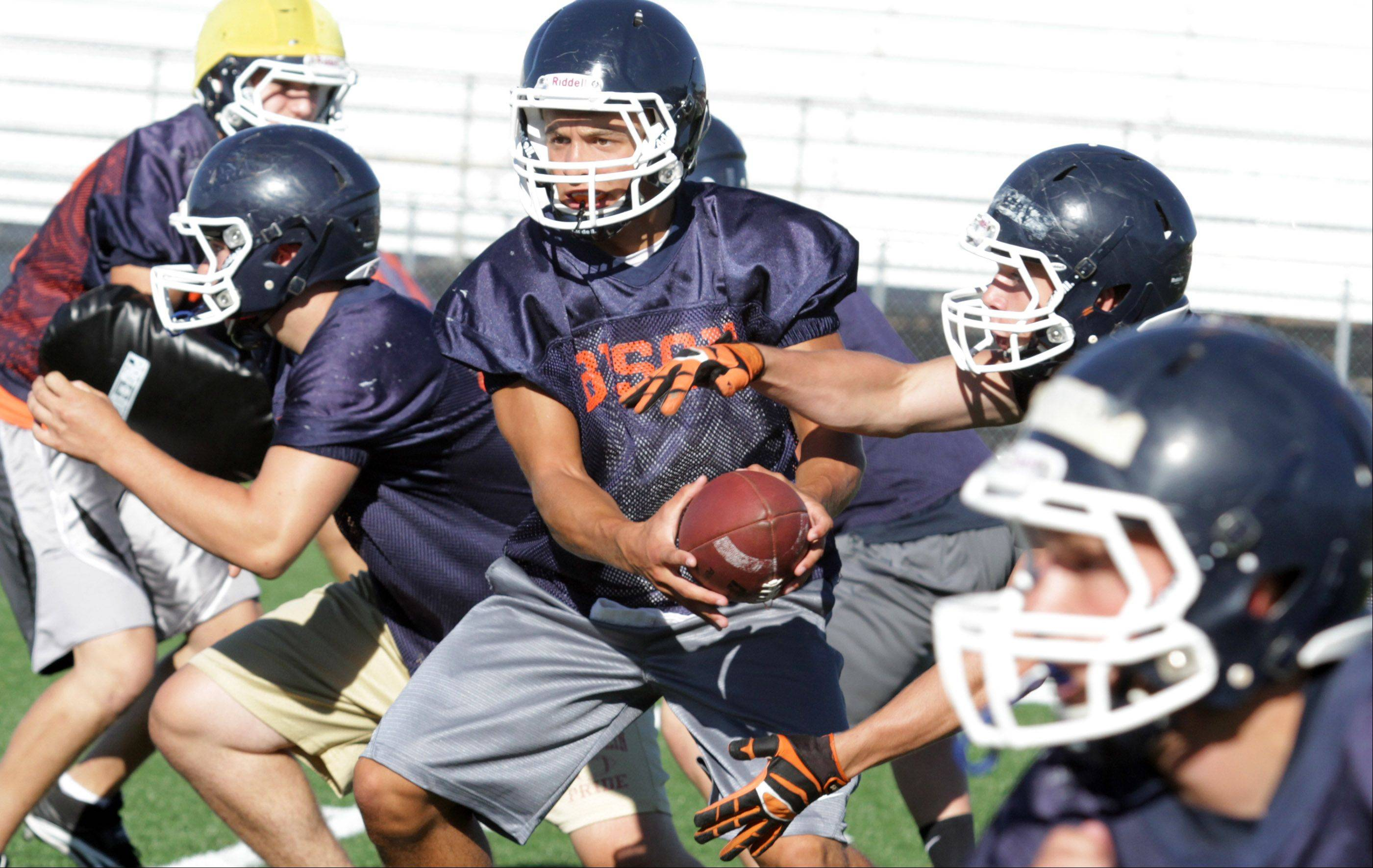 Buffalo Grove High School starting quarterback Andrew Apel hands the ball off to fullback Scott Smitheren during the first day of practice on Wednesday, August 14, 2013.