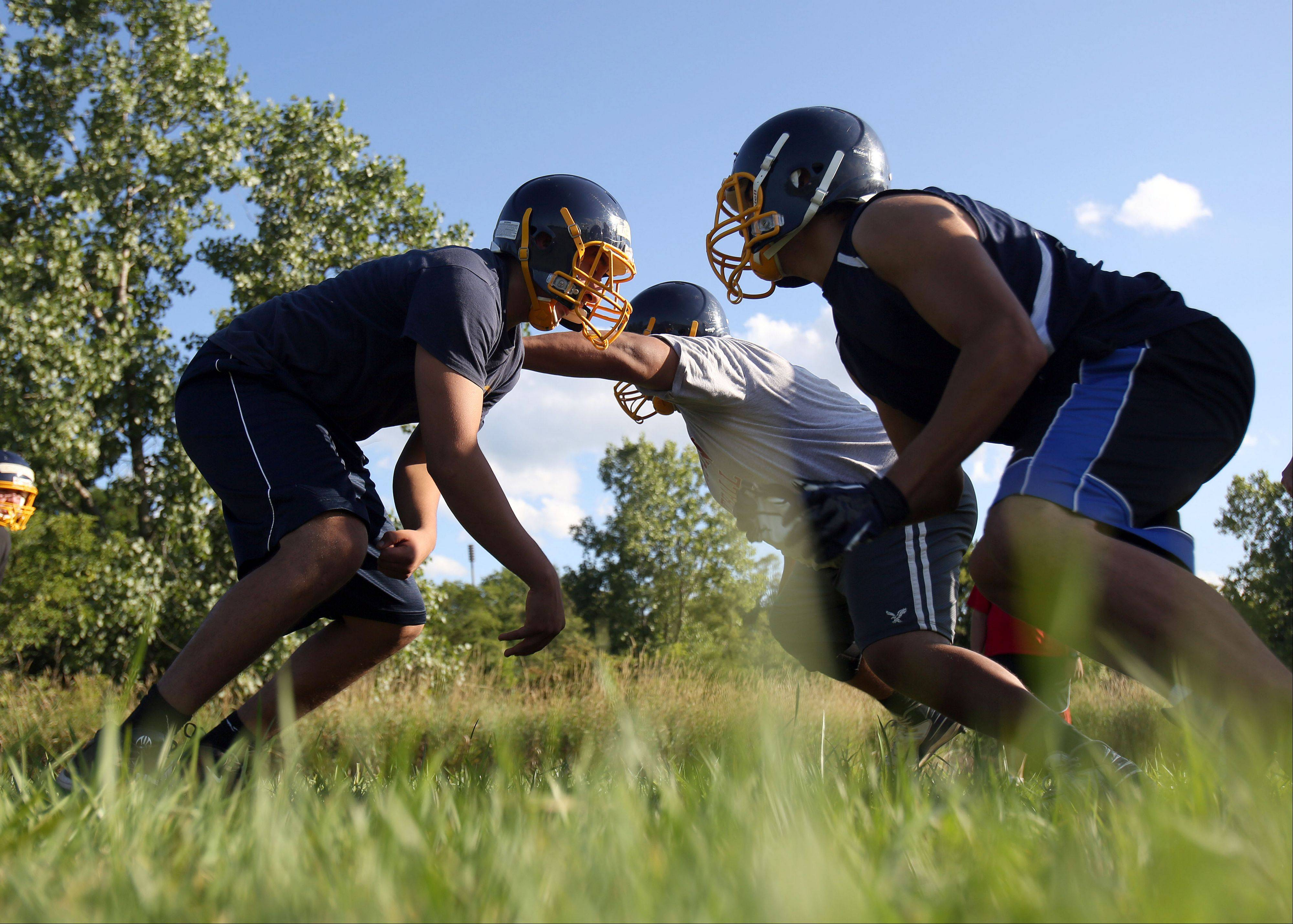 Players run through plays during the first day of football practice Wednesday at Round Lake High School.