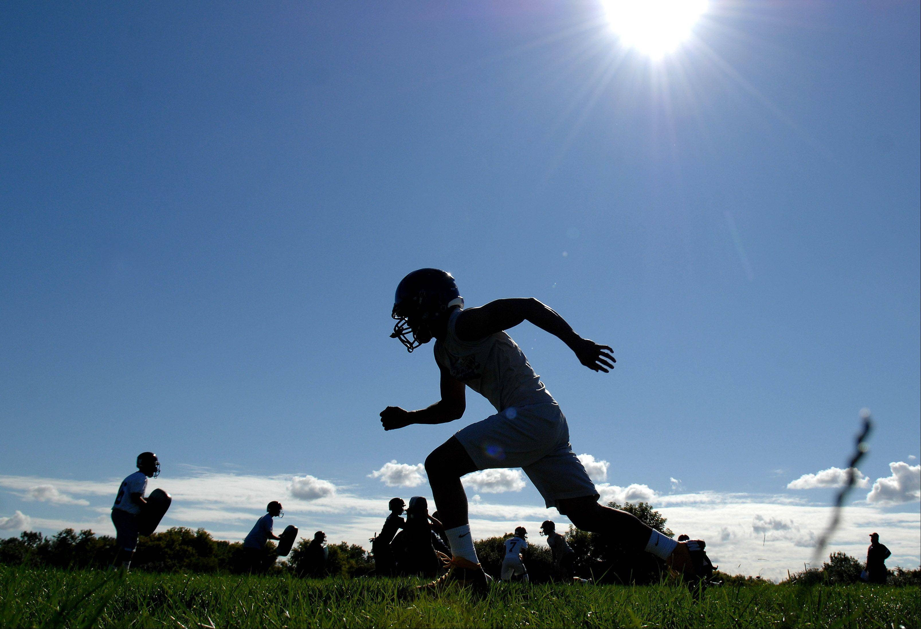 The offense runs through plays during the first day of fall football practice at Bartlett High School Wednesday.