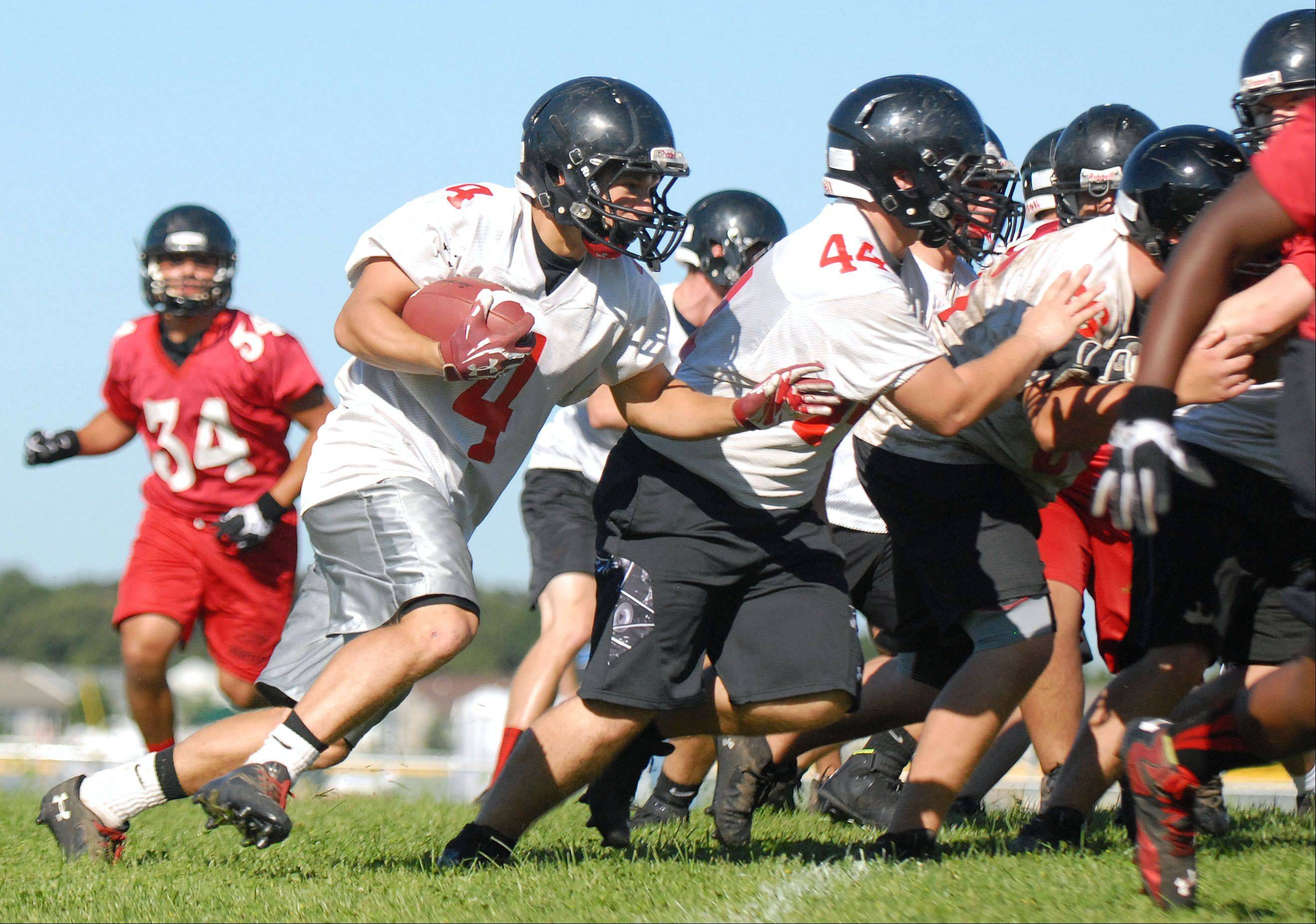 Senior Mitchell Kawell takes off with the ball during the first day of practice for Huntley High School varsity football on Wednesday, August 14.