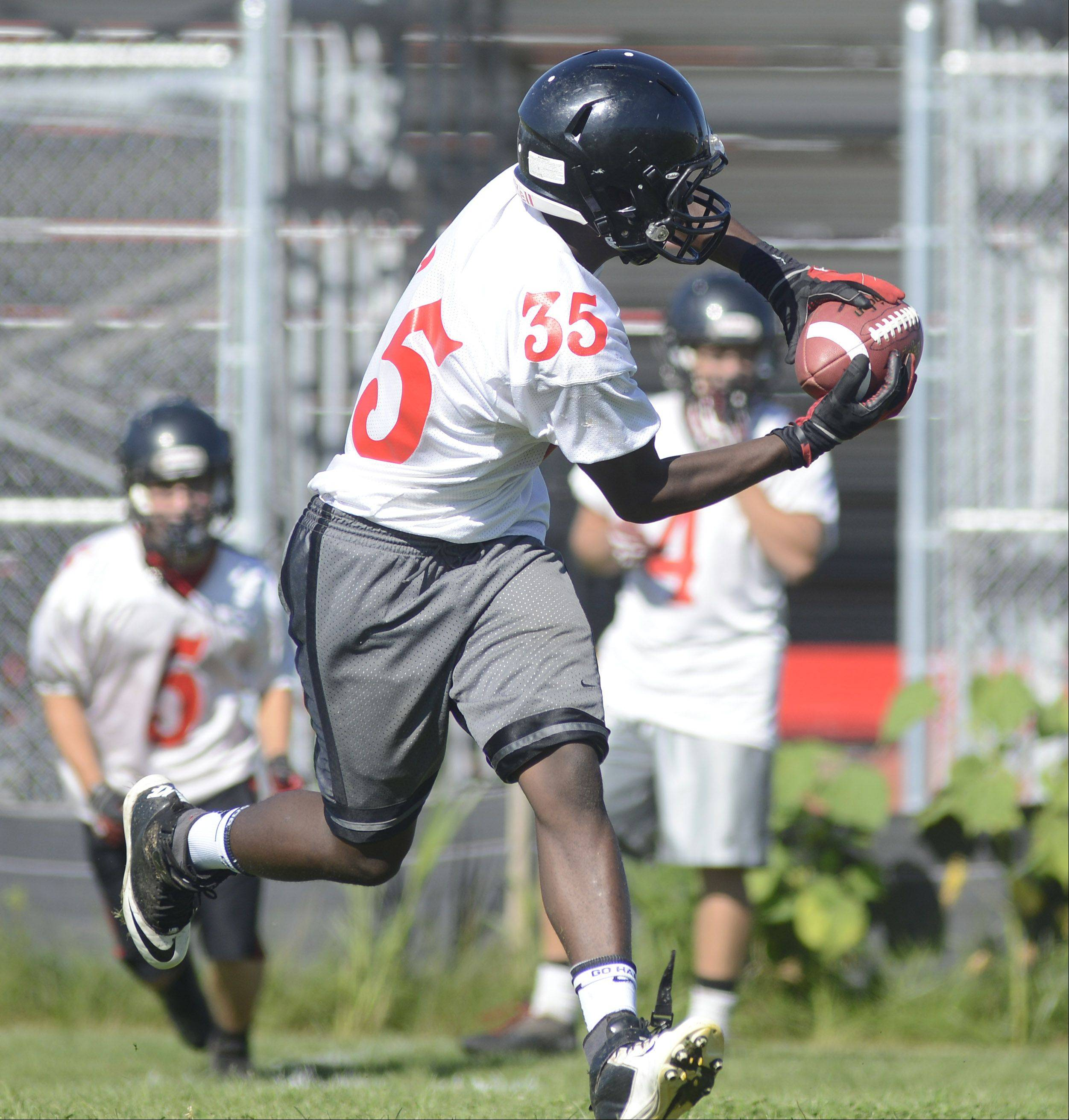 Junior Josh Esi catches the ball (framing teammate senior Mitchell Kawell in background) during a speed drill for varsity football's first day of practice at Huntley High School on Wednesday, August 14.