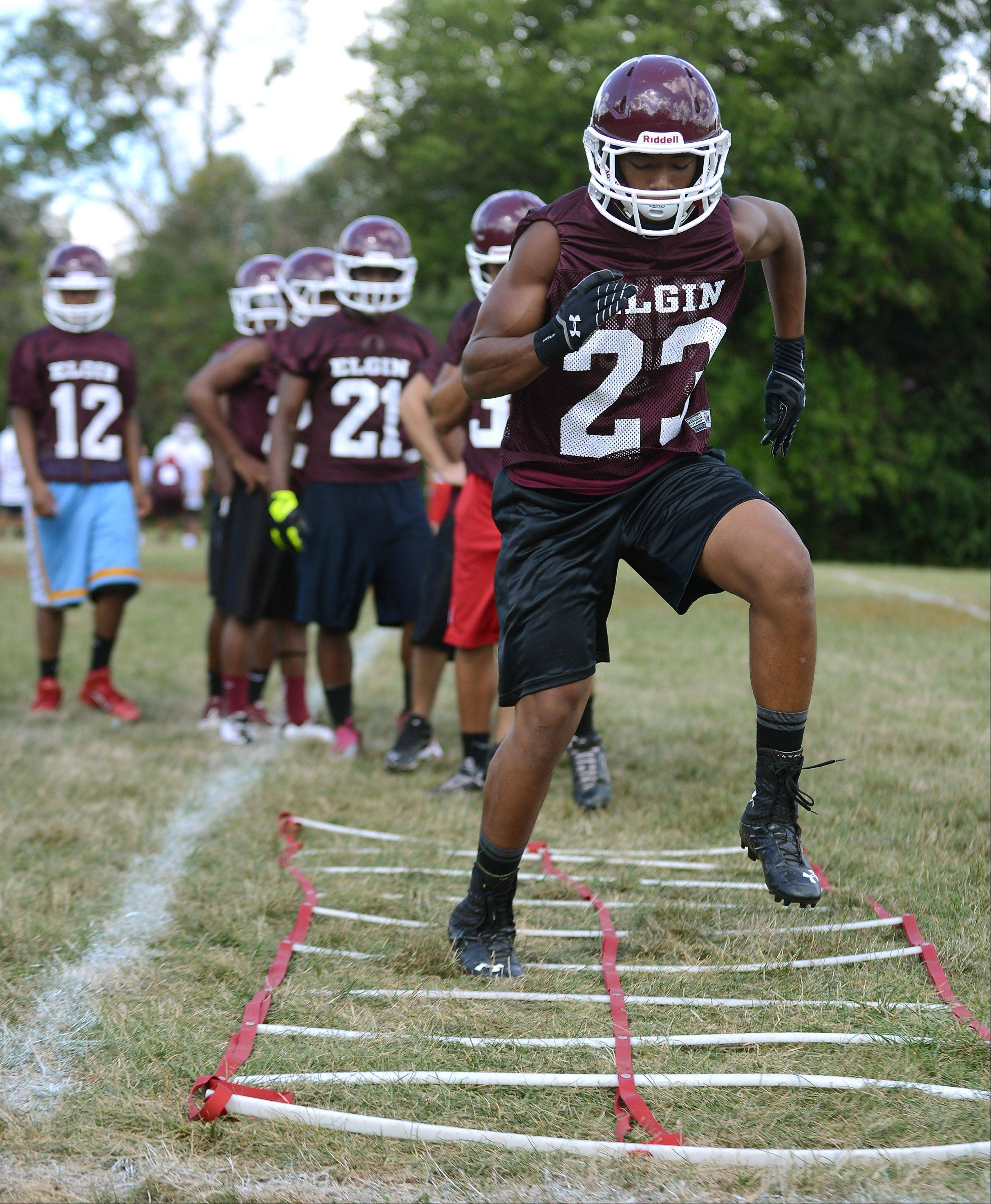 Jordan Smith runs the ladder during the first day of fall football practice at Elgin High School Wednesday.
