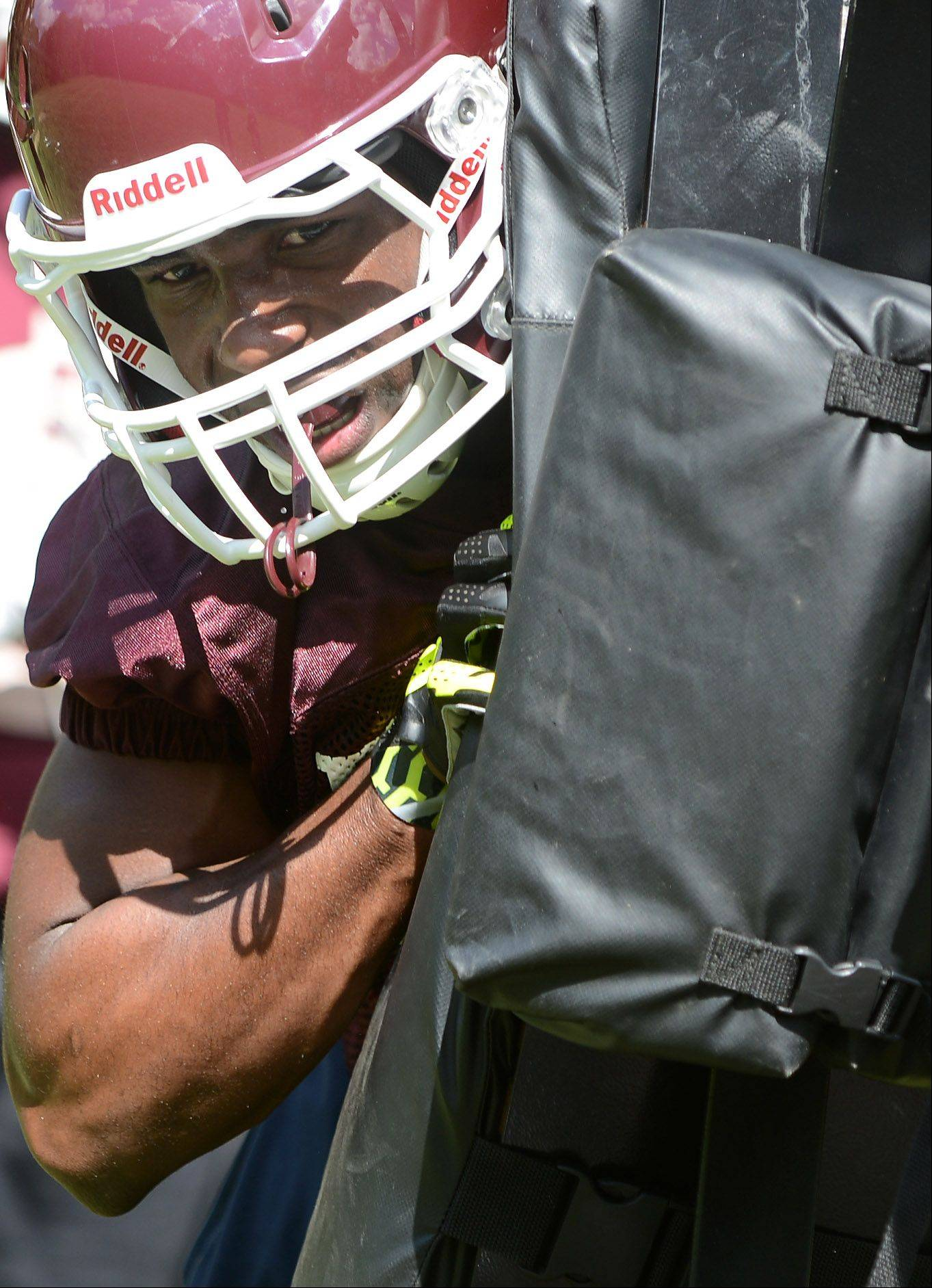 Jaylen Clemons drives the blocking sled back during the first day of fall football practice at Elgin High School Wednesday.