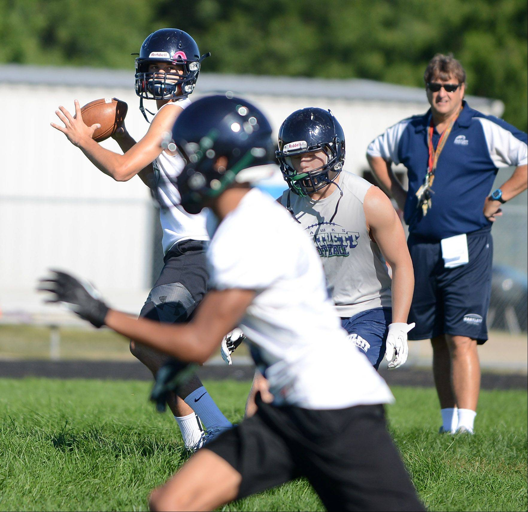 Quarterback Jordan Flint delivers a pass during the first day of fall football practice at Bartlett High School Wednesday.
