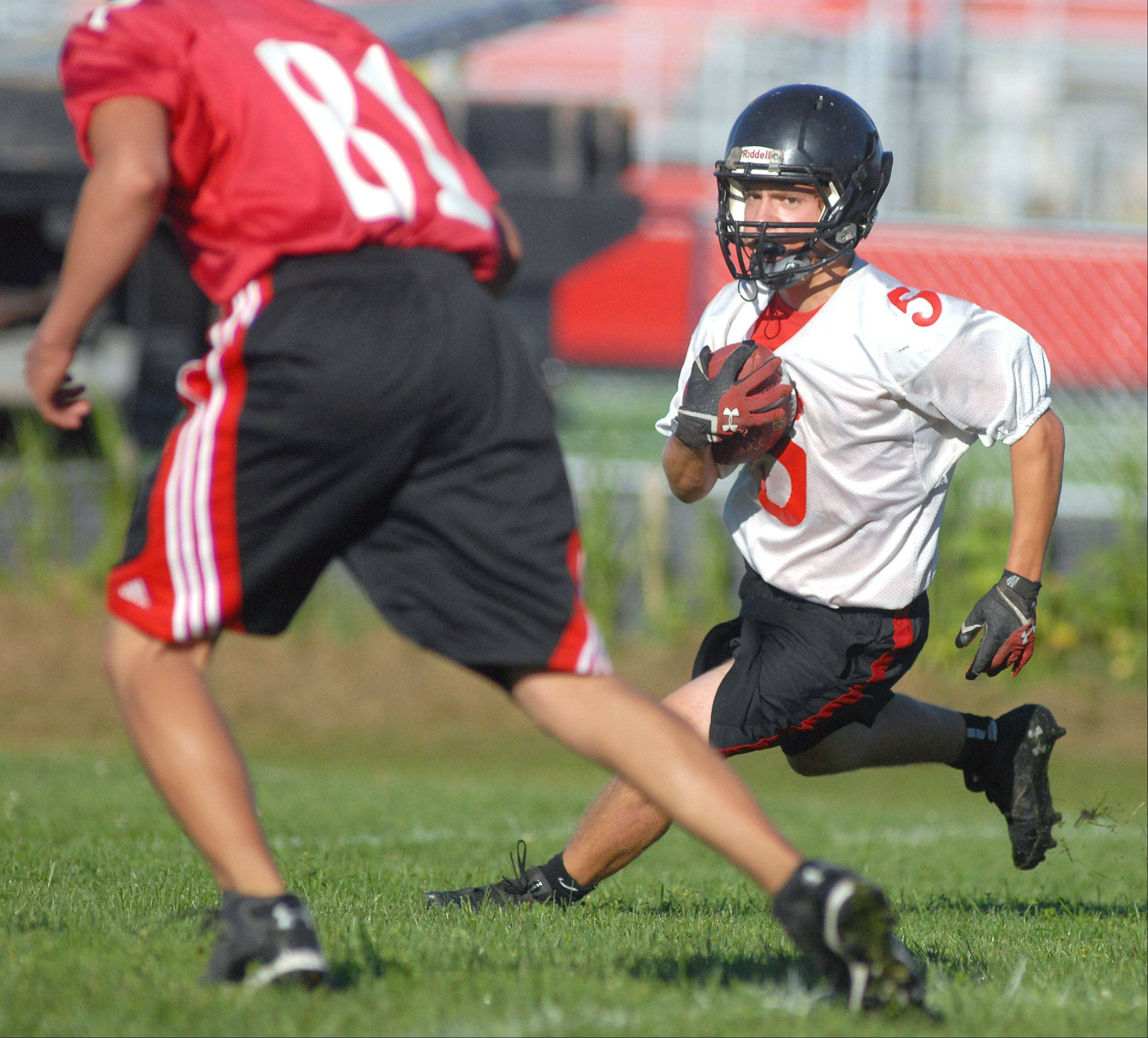 Senior Jake Scalise looks to avoid junior Conner Young during varsity football's first day of practice at Huntley High School on Wednesday, August 14.