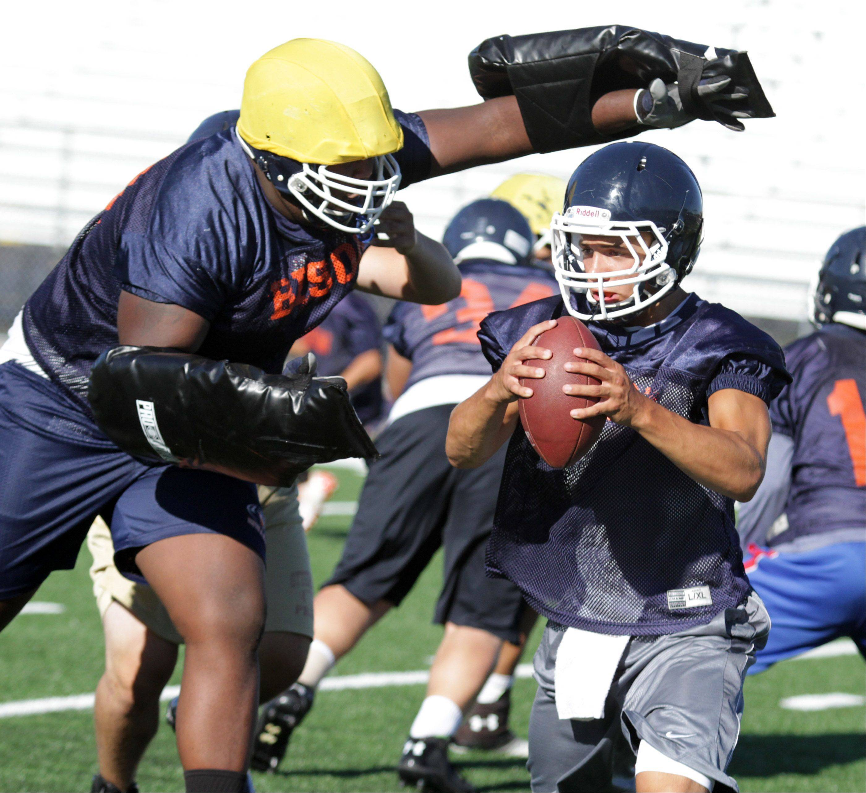 Buffalo Grove High School starting quarterback Andrew Apel tries to escape the defensive line .