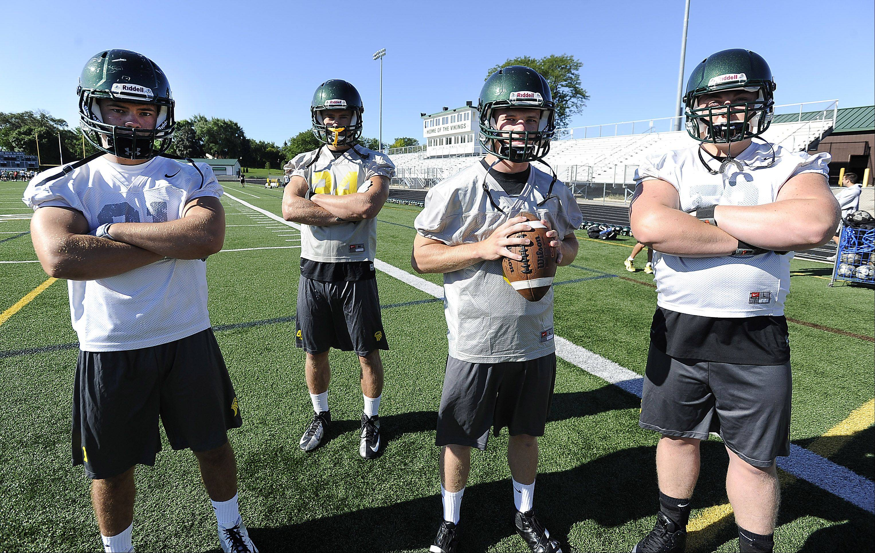 Fremd football players quarterback Sam Beutler, center, with teammates Jeff McGlade, running back, Matt Konopka, linebacker and Brad Ruehrdanz, offensive tackle take the field.
