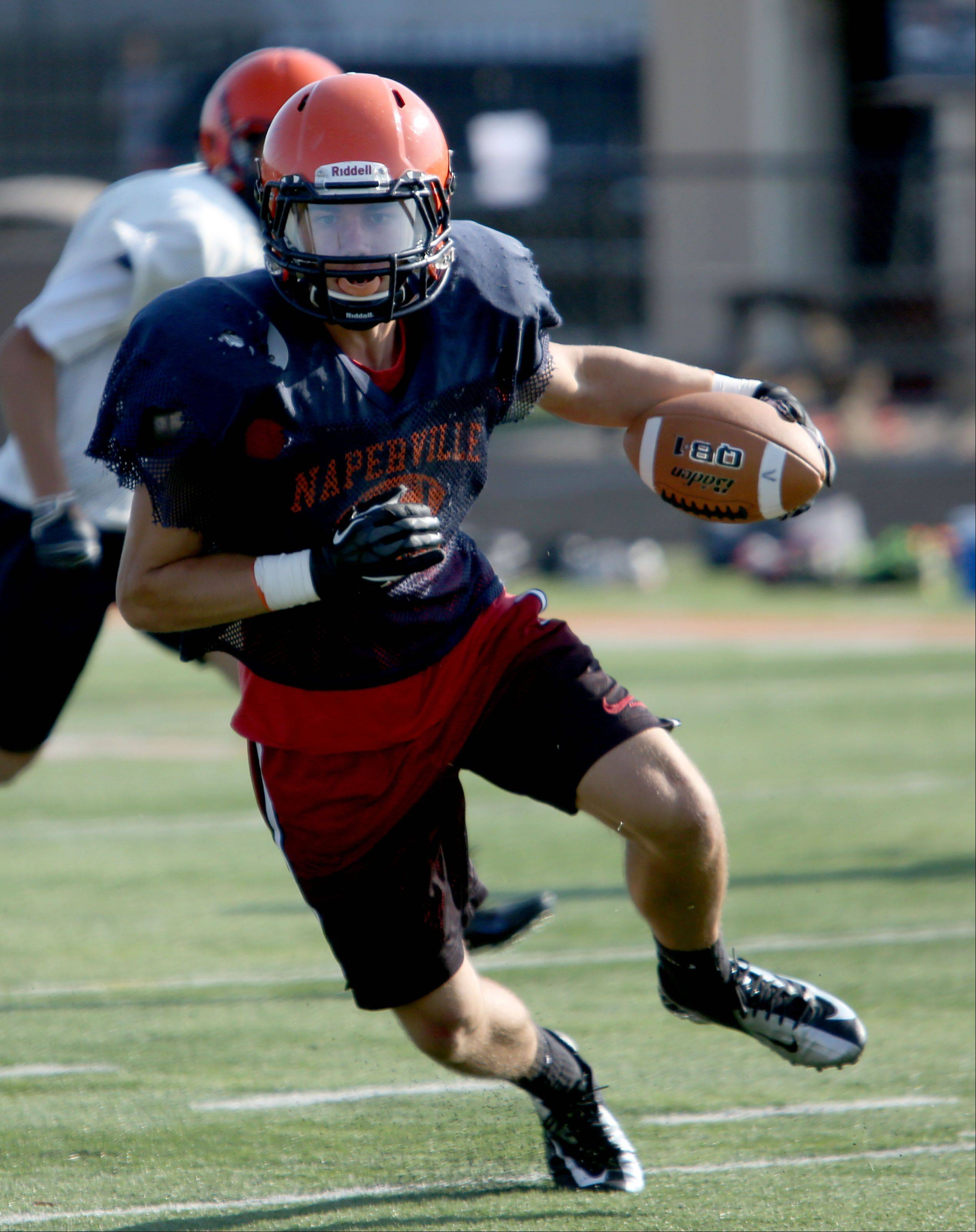 Danny Schertz runs a drill during Naperville North football practice.