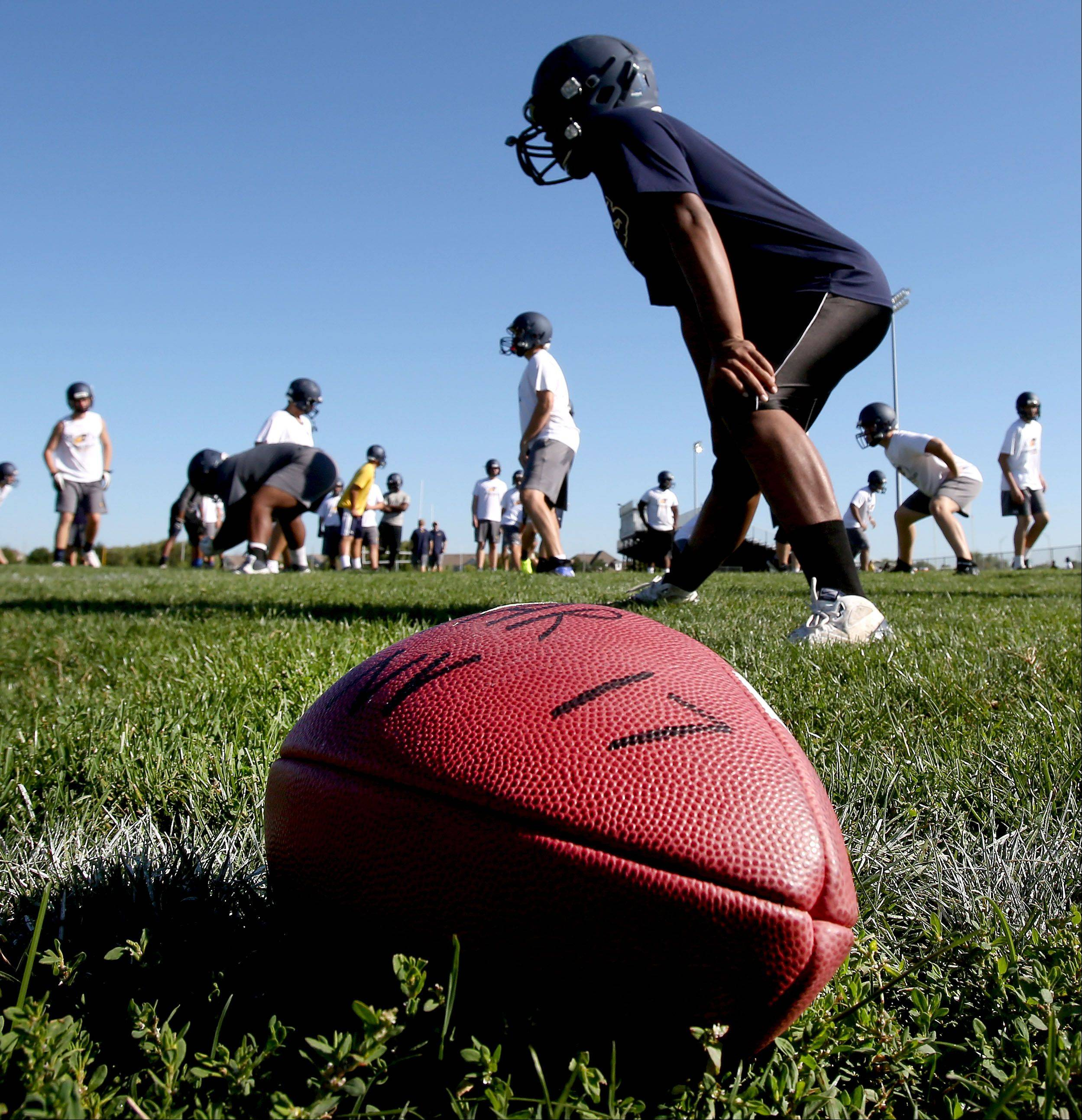 The Neuqua Valley football team warms up before the first day of practice.