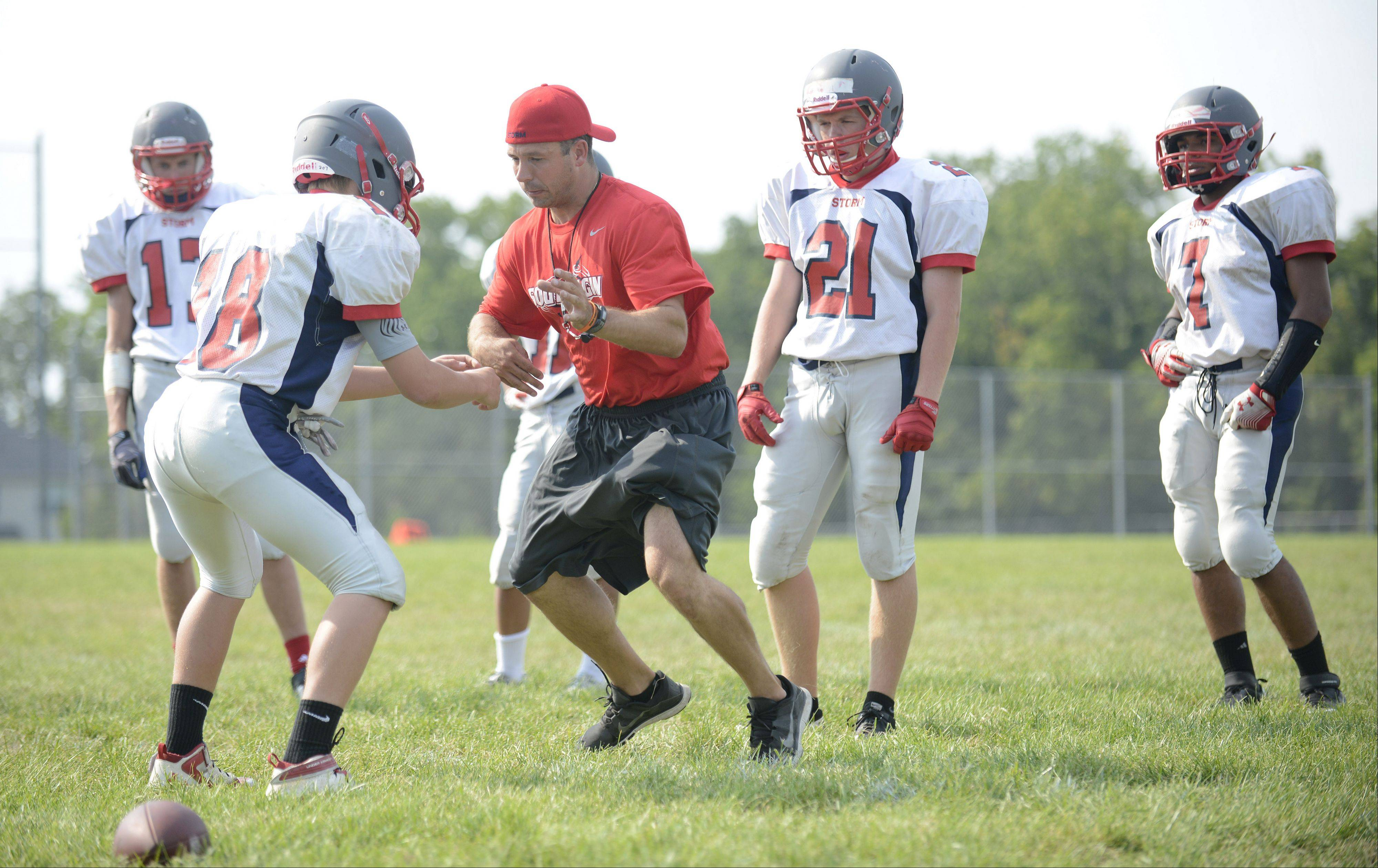 New South Elgin varsity football coach Pat Pistorio shows players how to break away from an opponent's grip during practice.