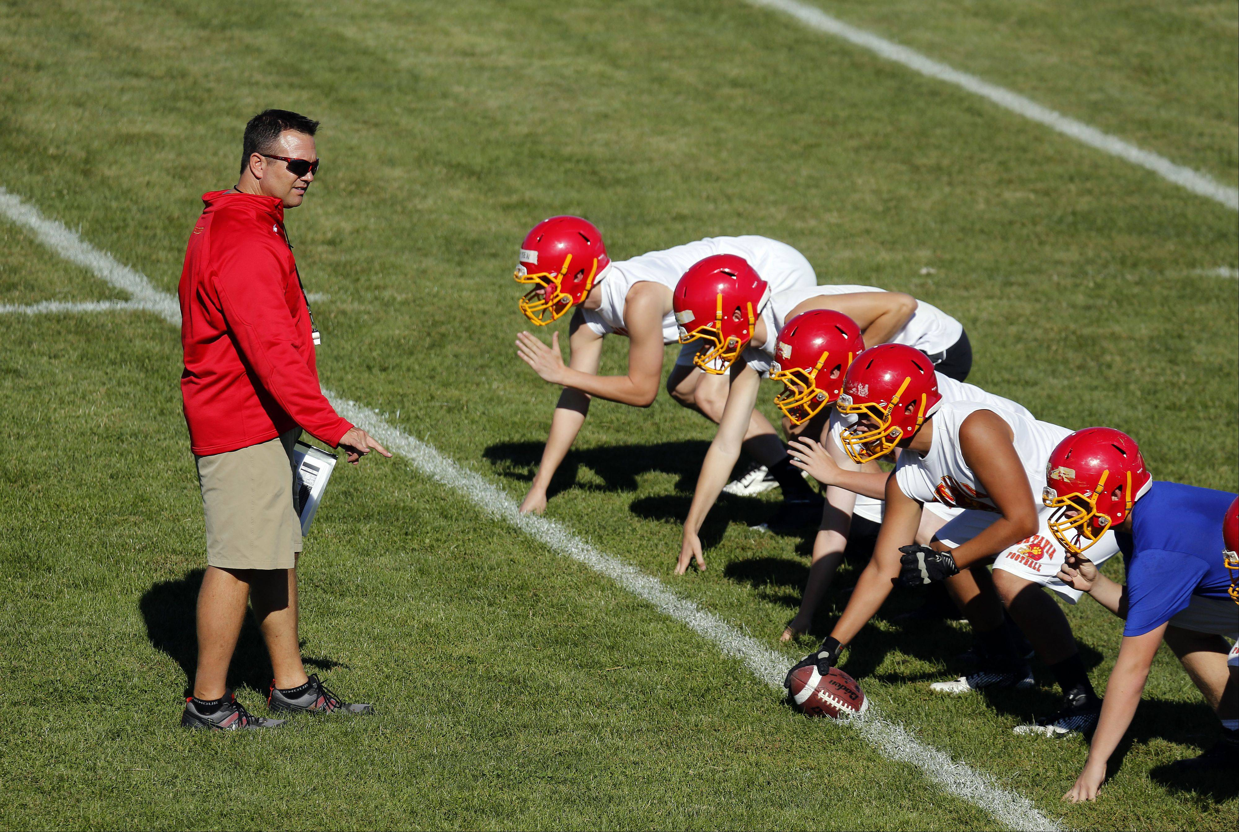 Brian Hill/bhill@dailyherald.comBatavia coach Dennis Piron works with his team during the first day of football practice at Batavia High School Wednesday.
