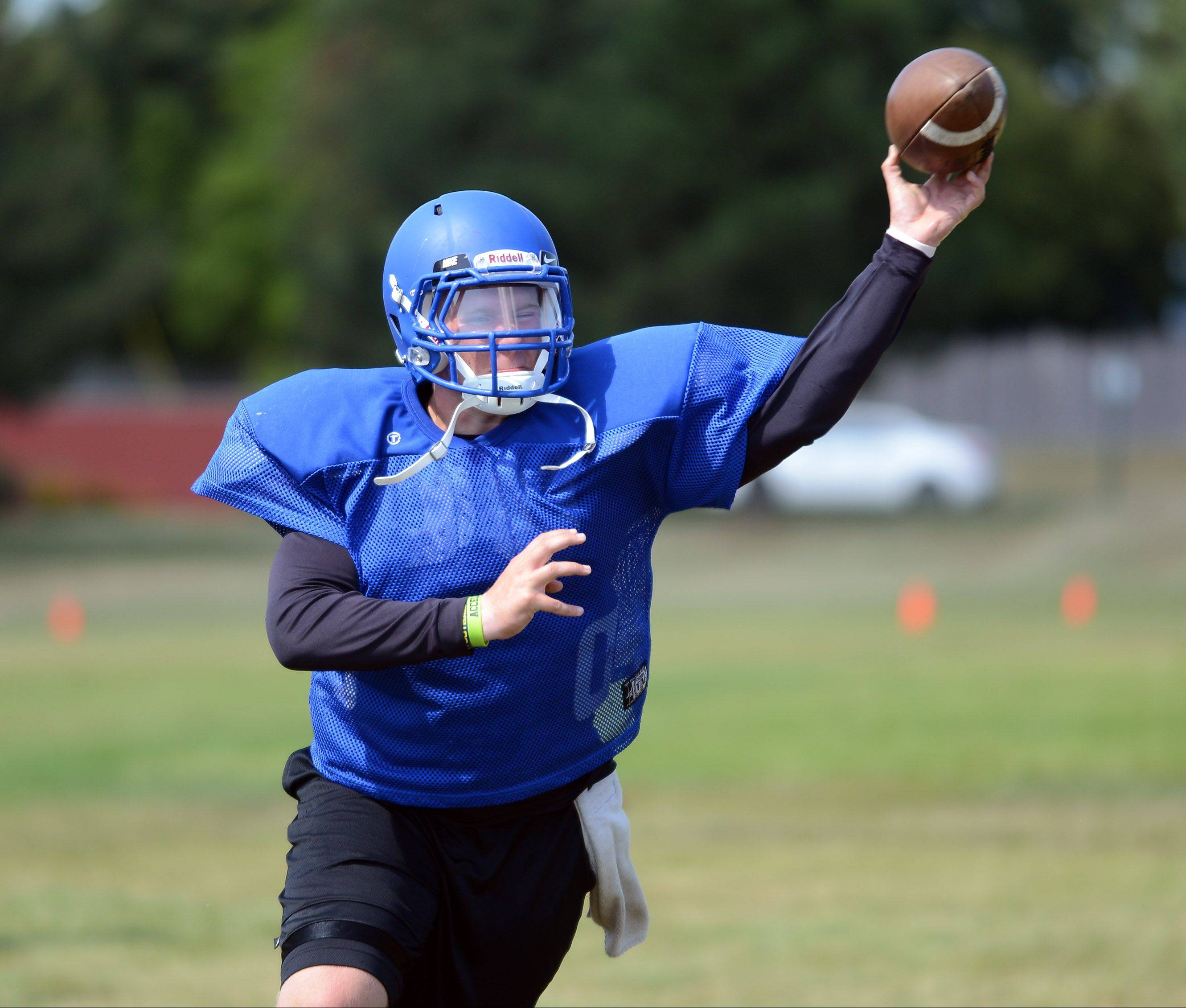 Quarterback Kyle Riley flings a pass during Aurora Central Catholic football practice Friday.
