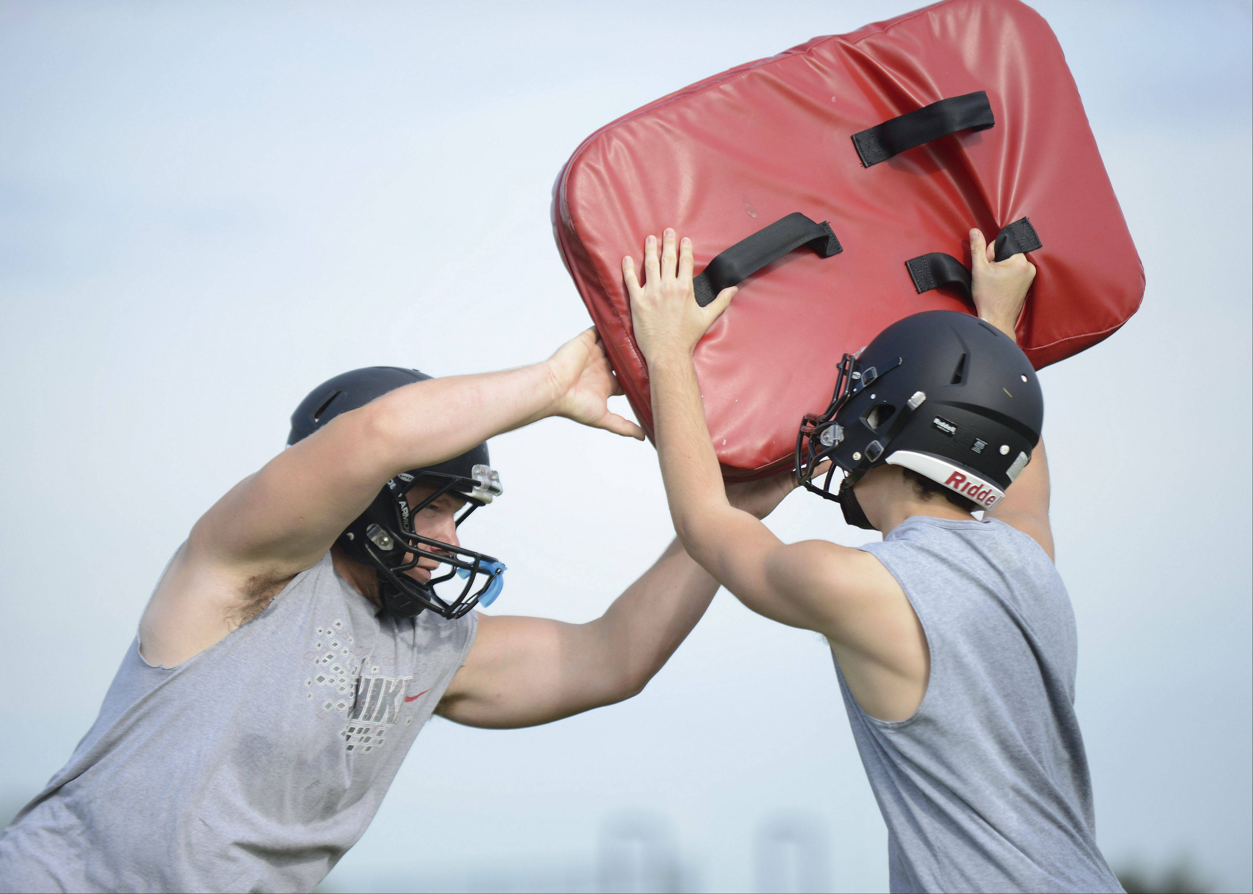 Juniors Zack Thielk, left, and Tarkan Cetinel during Kaneland High School's varsity football practice on Thursday, August 15.
