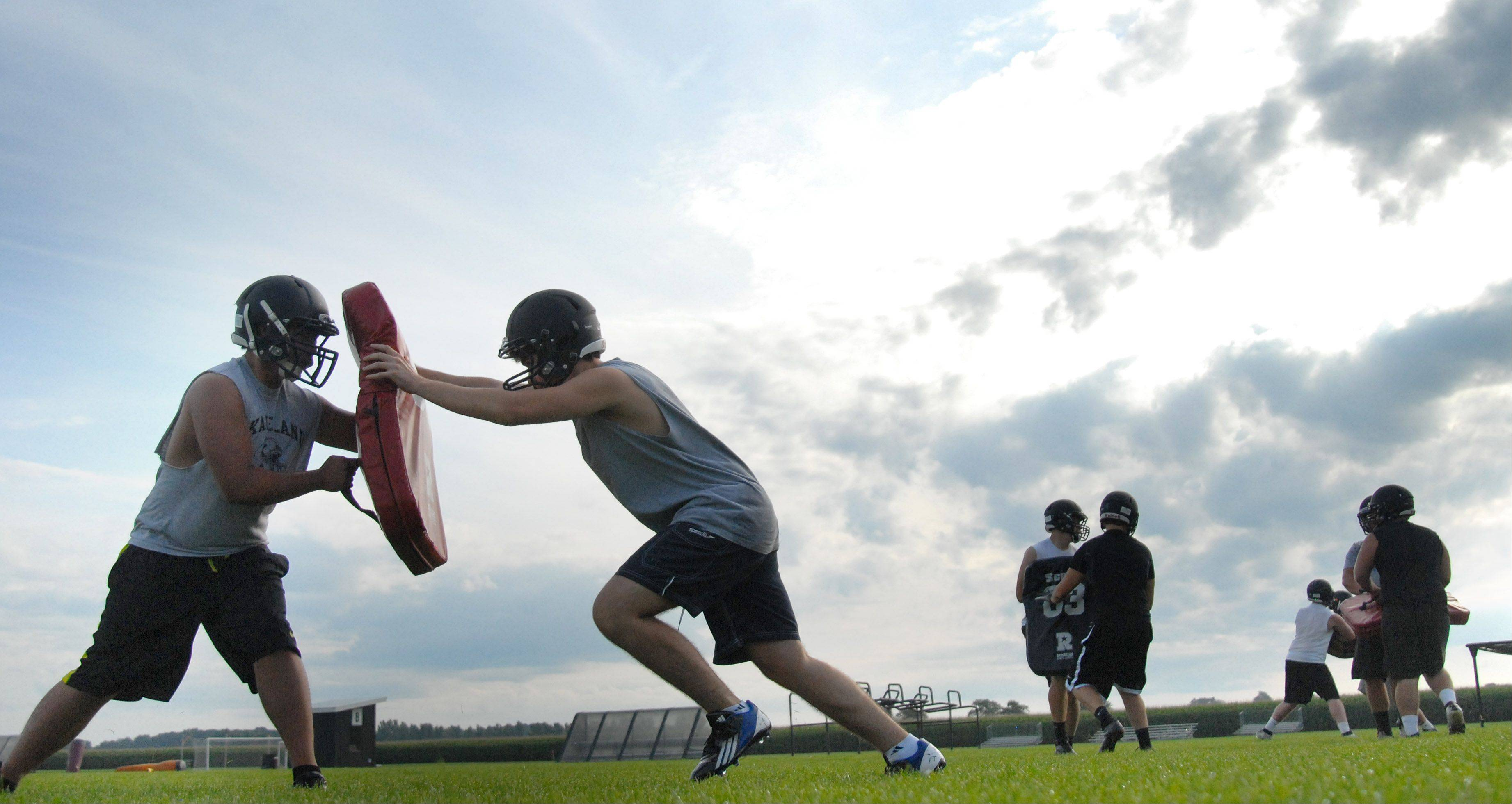 Sophomore Jake Gomes, left, and junior Tarkan Cetinel during Kaneland High School's varsity football practice on Thursday, August 15.