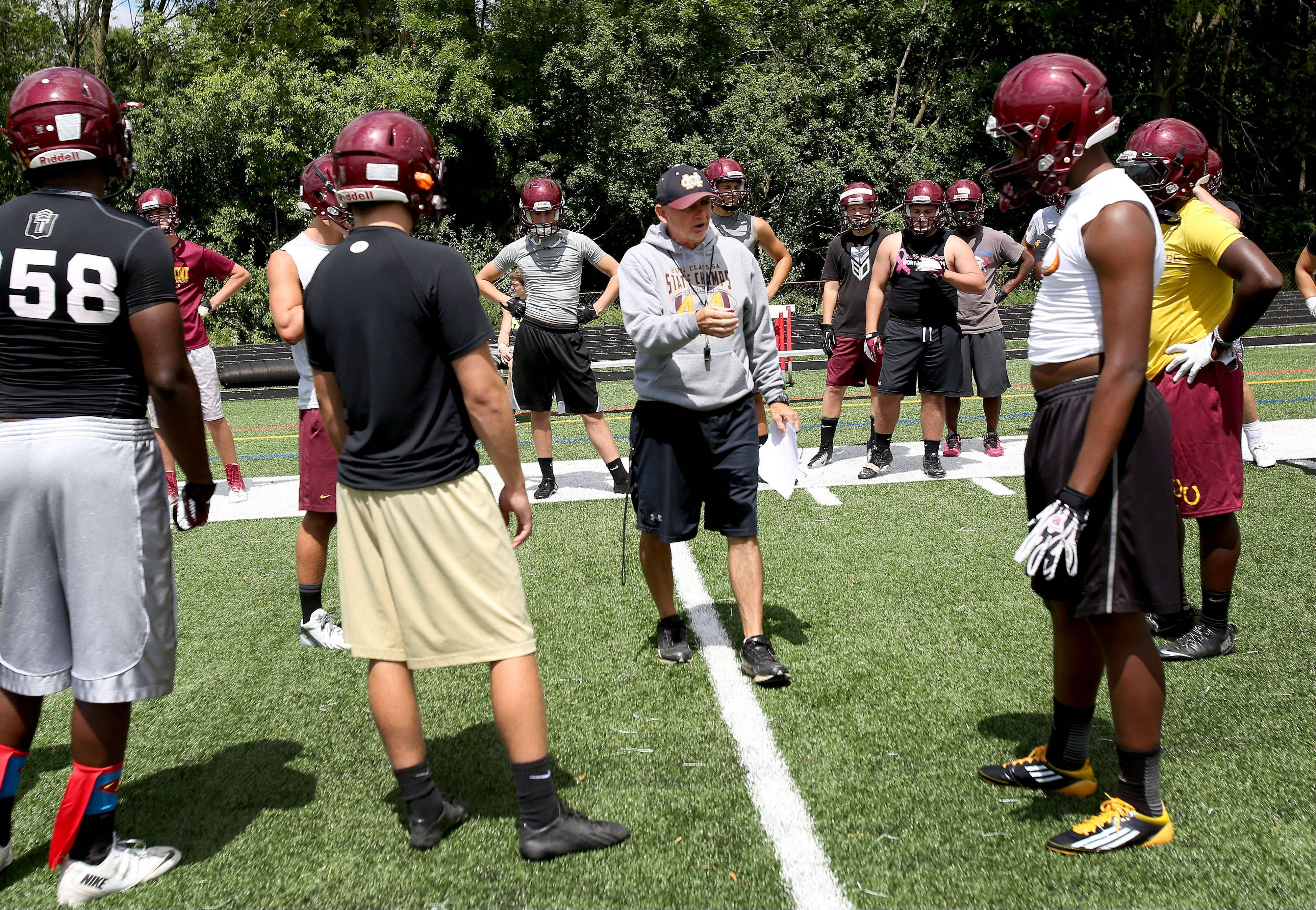 Coach Chris Andriano gets the team started at the first Montini football practice of the season.