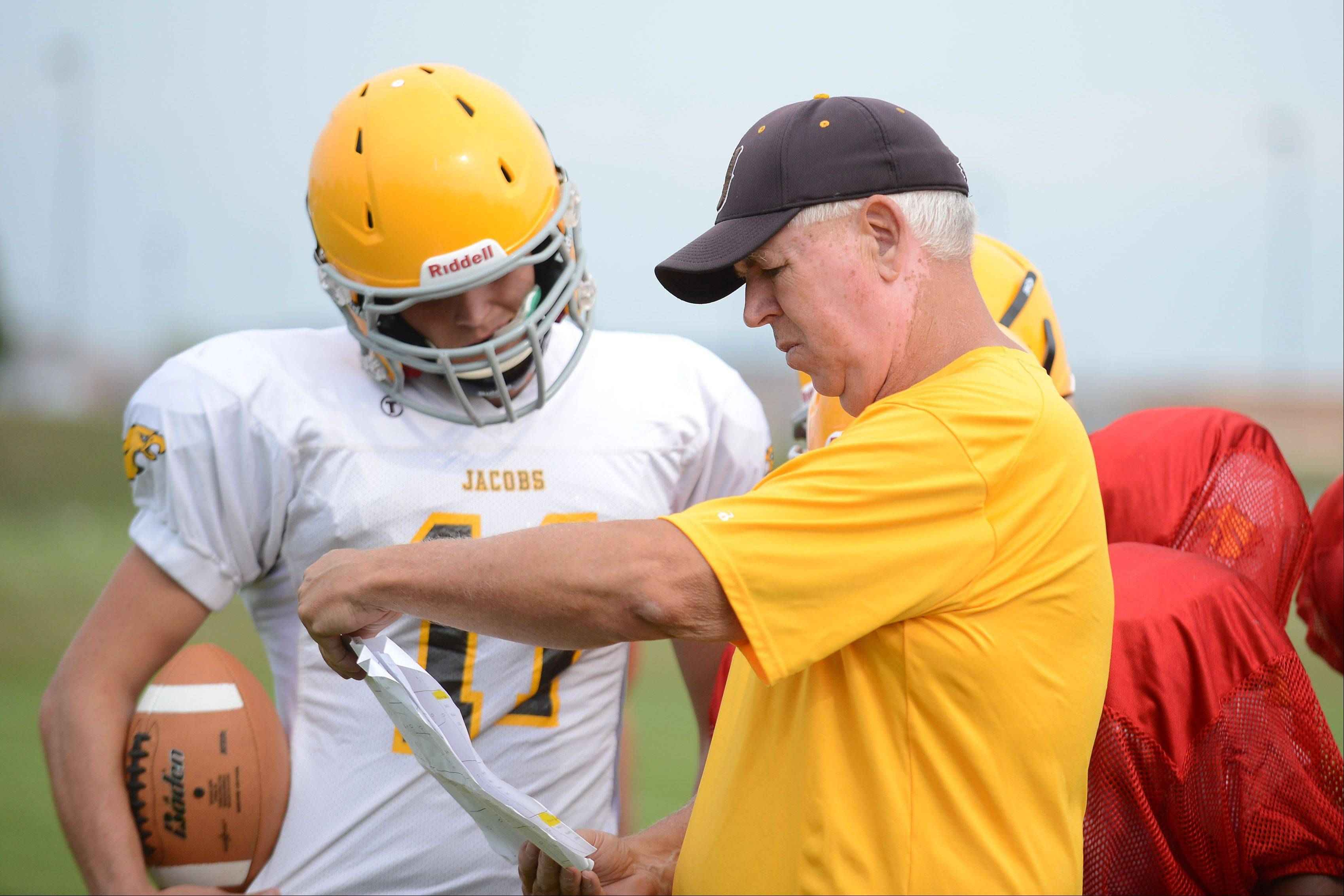 Quarterback Bret Mooney and coach Bill Mitz go over a play during Jacobs High School football practice in Algonquin.