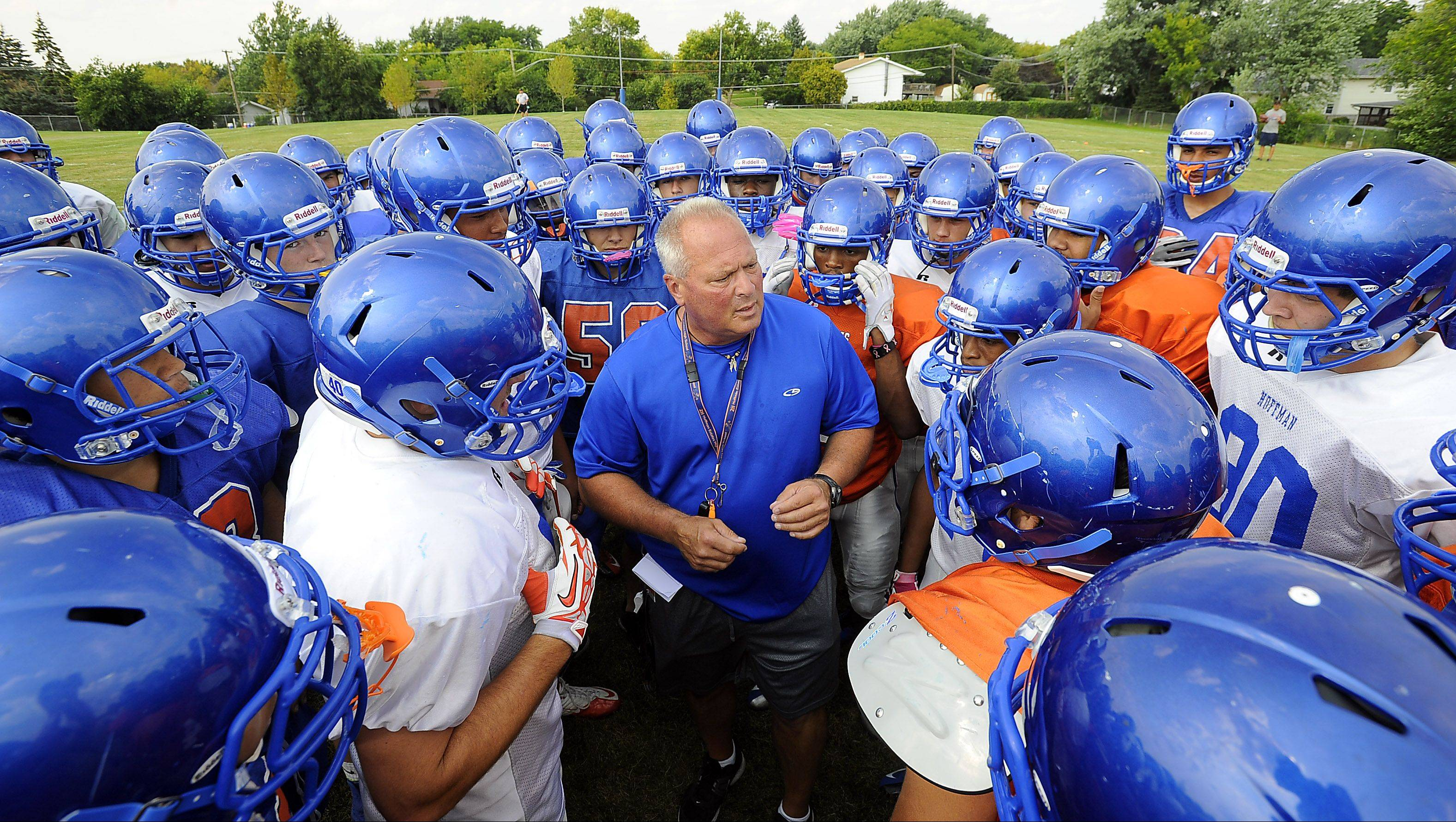Hoffman Estates coach Mike Donatucci gathers his players as the Hawks embark a new chapter in the school's football history.