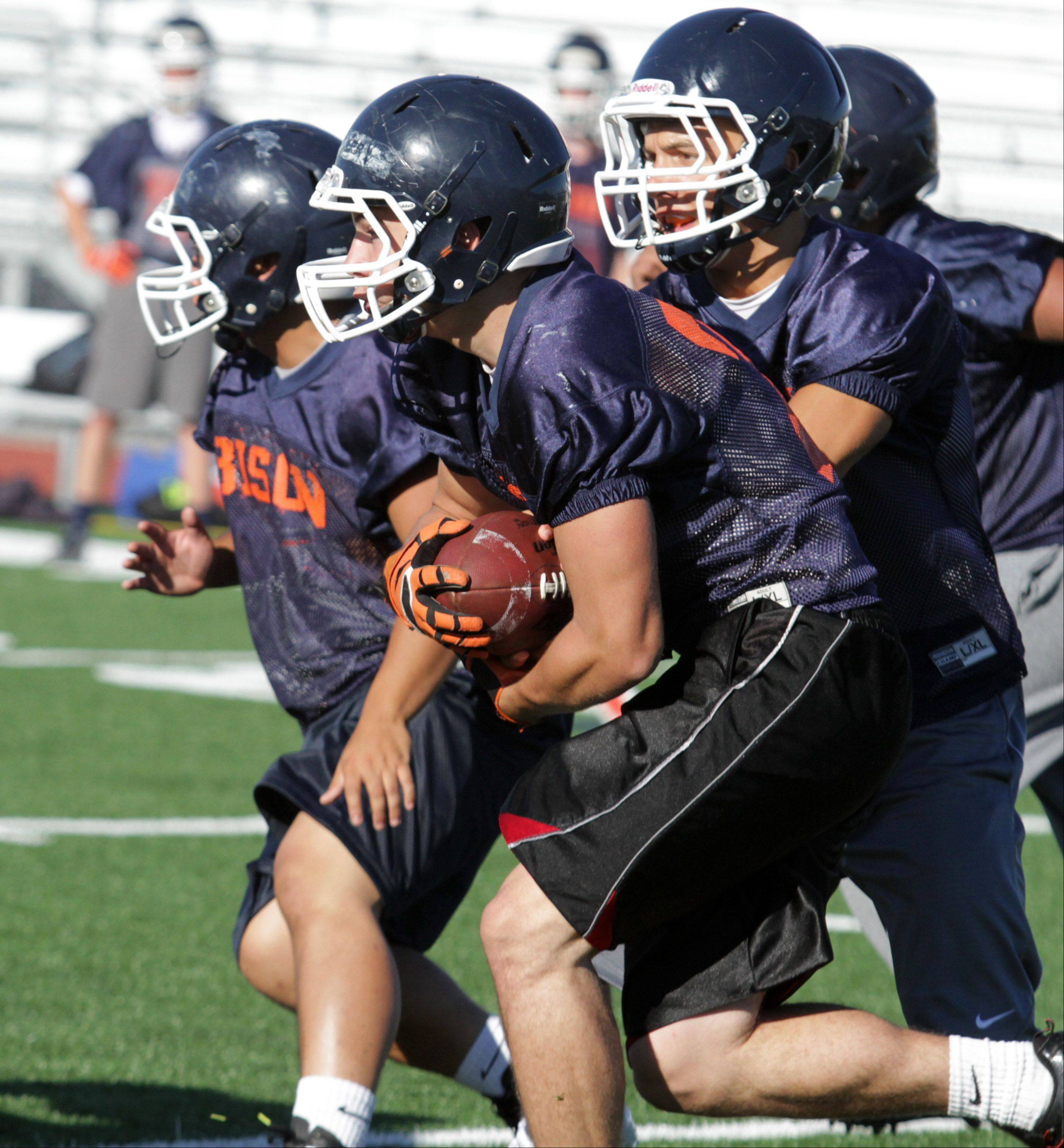 Buffalo Grove quarterback Andrew Apel hands the ball off to fullback Scott Smitheren in preparation for Friday's home opener against Leyden.