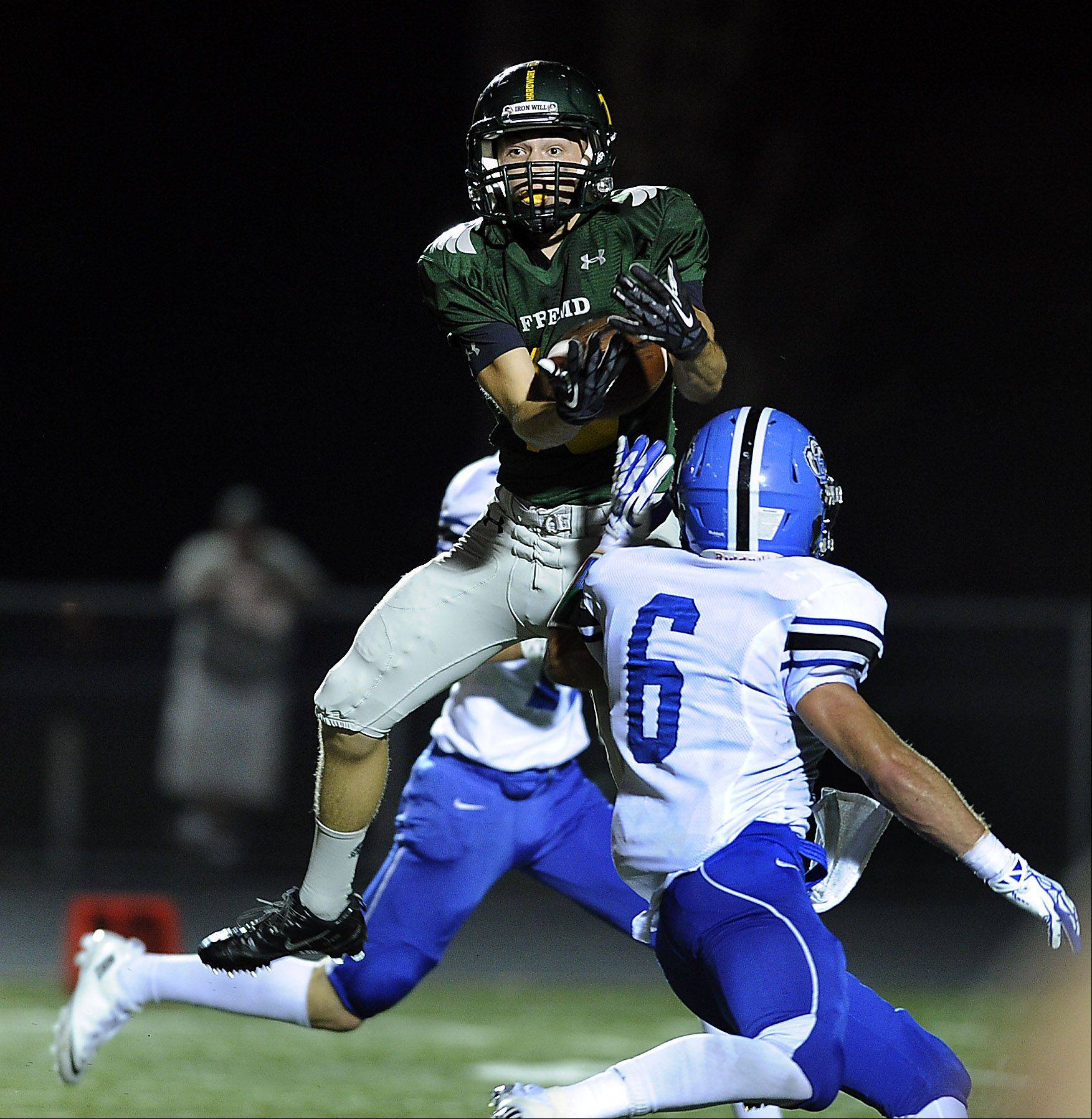 Fremd's Anthony Halvorsen hauls in a pass in the first quarter despite Lake Zurich's Sean Lynch attempts to defend him in a season opener at Fremd on Friday.