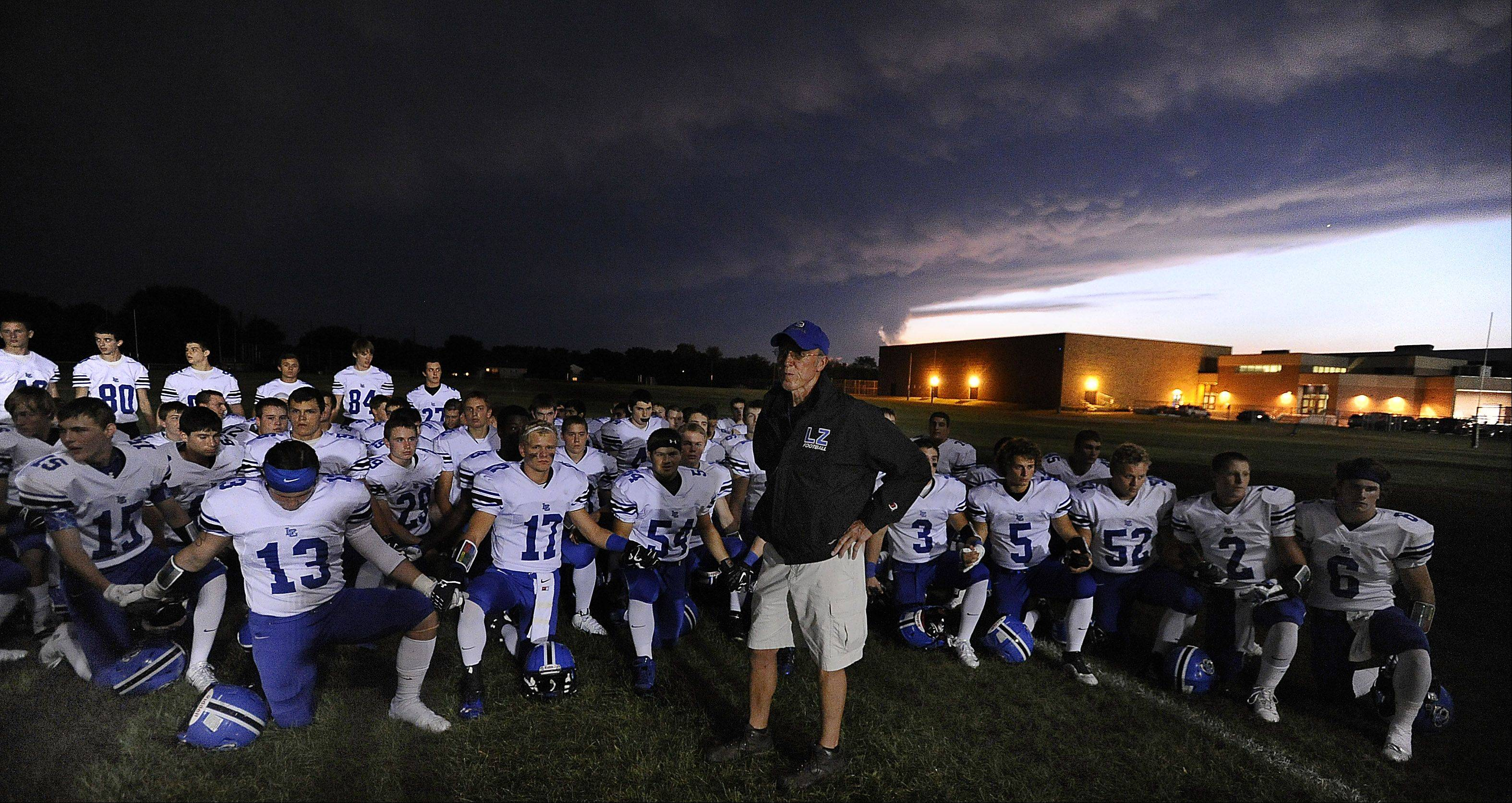 Mark Welsh/mwelsh@dailyherald.comLake Zurich coach Dave Proffitt stands with his players before the game as storm clouds rumble overhead Friday at Fremd.