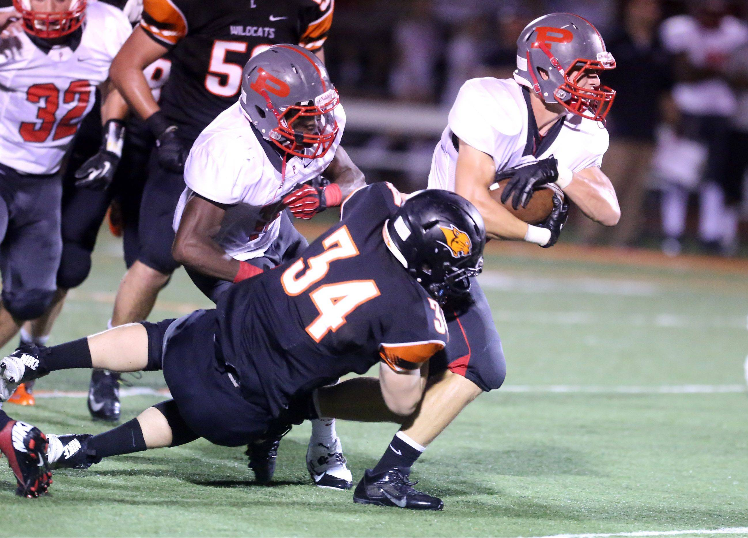 Palatine's Joshua Mackie is dragged down by Libertyville defender Matt Pierson during the first half at Libertyville on Friday.