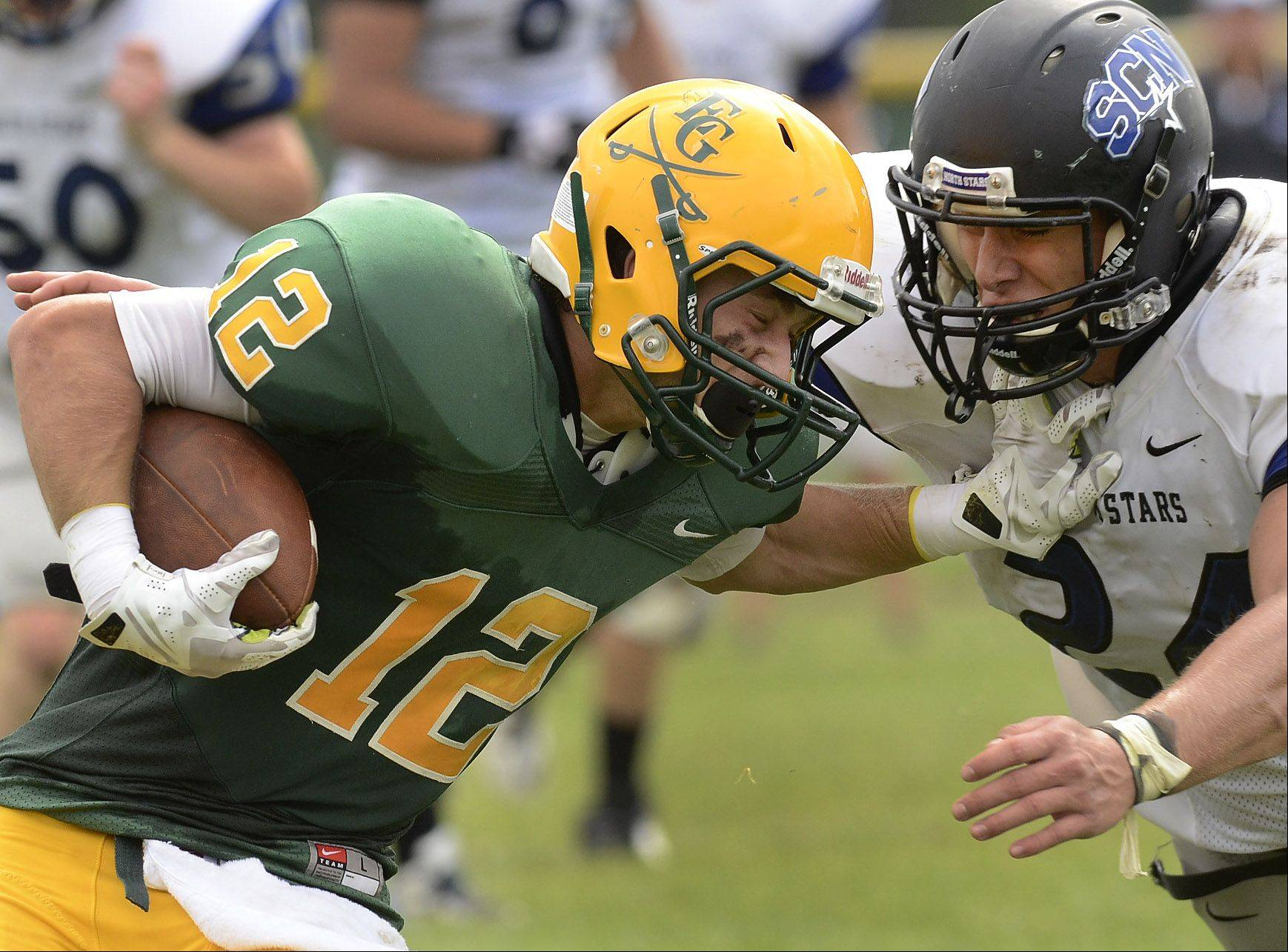 Matt Wary of Elk Grove rams into Evan Kurtz of St. Charles North on Saturday.