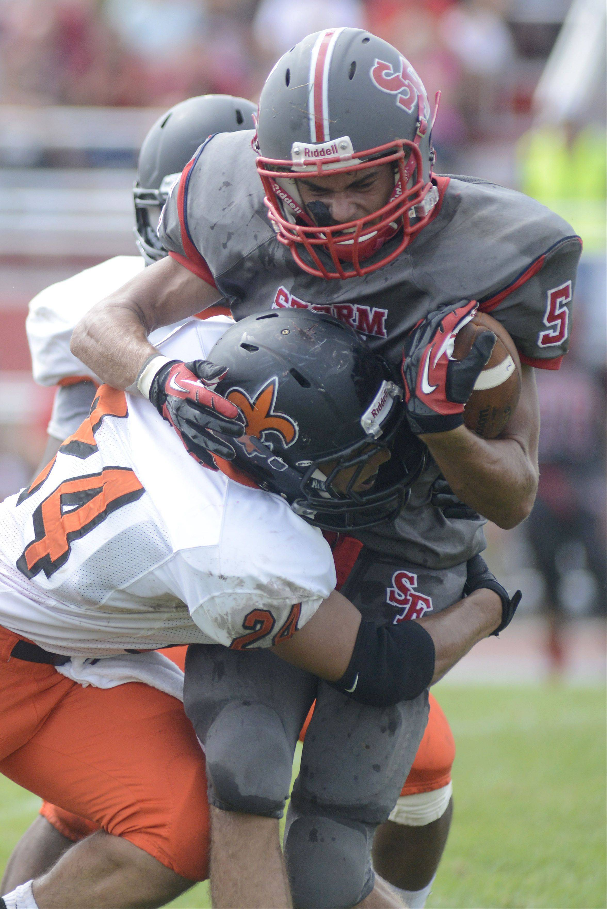 South Elgin's Tyler Christensen is sacked by St. Charles East's Ramon Lopez in the second quarter on Saturday, August 31.