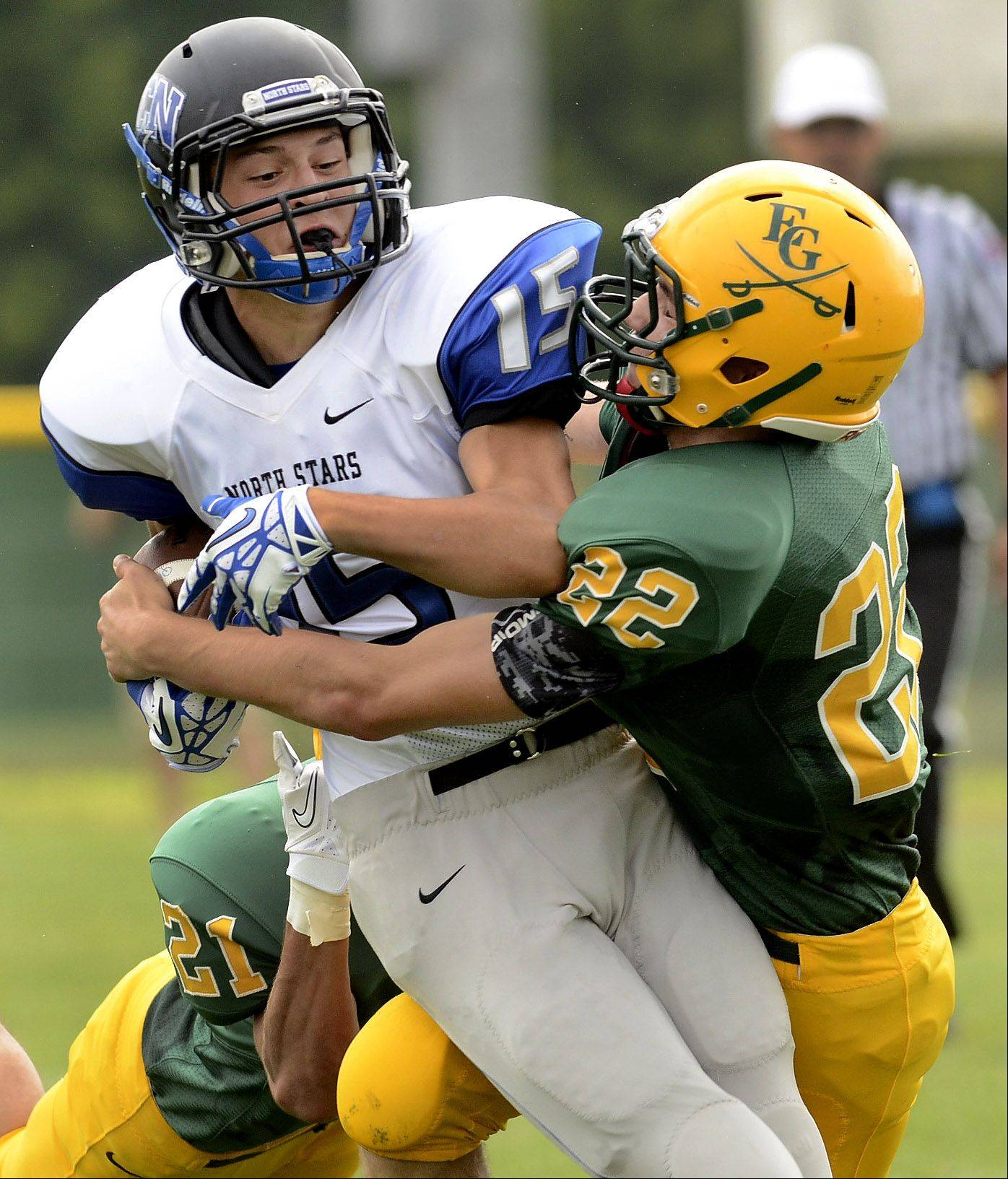 Elk Grove's Sean Oldenburg wraps up John LeGare of St. Charles North.