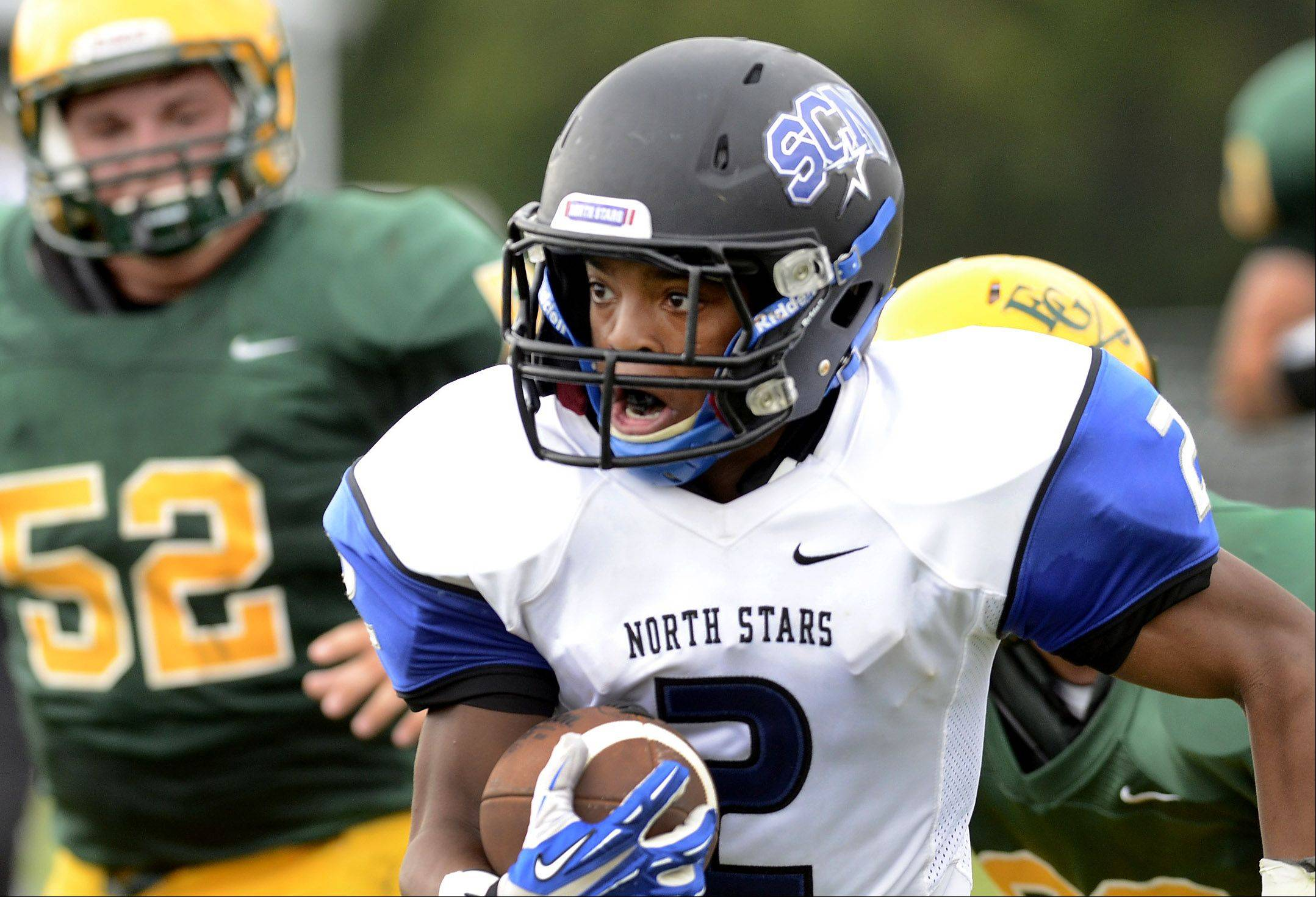 Nate Newbill of St. Charles runs after a catch during St. Charles North at Elk Grove football.