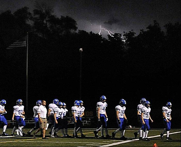 Storms linger in the background as Lake Zurich's players walk off the field during the season opener at Fremd High School on Friday.