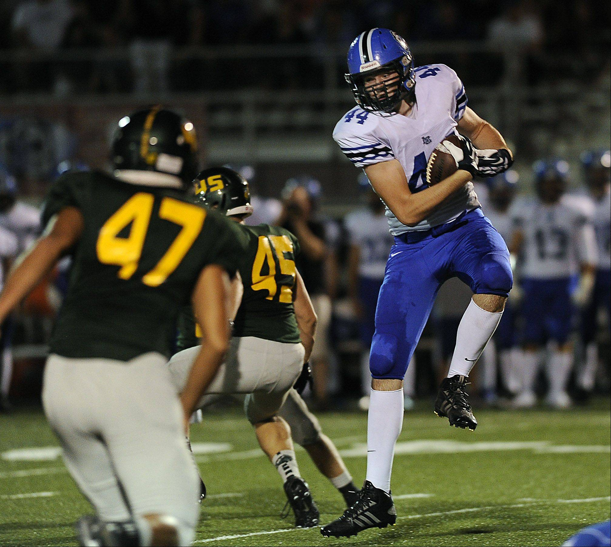 Lake Zurich's Zach Wallace hauls in a first quarter pass play against Fremd's defense in the opening day game at Fremd High School in Palatine on Friday.