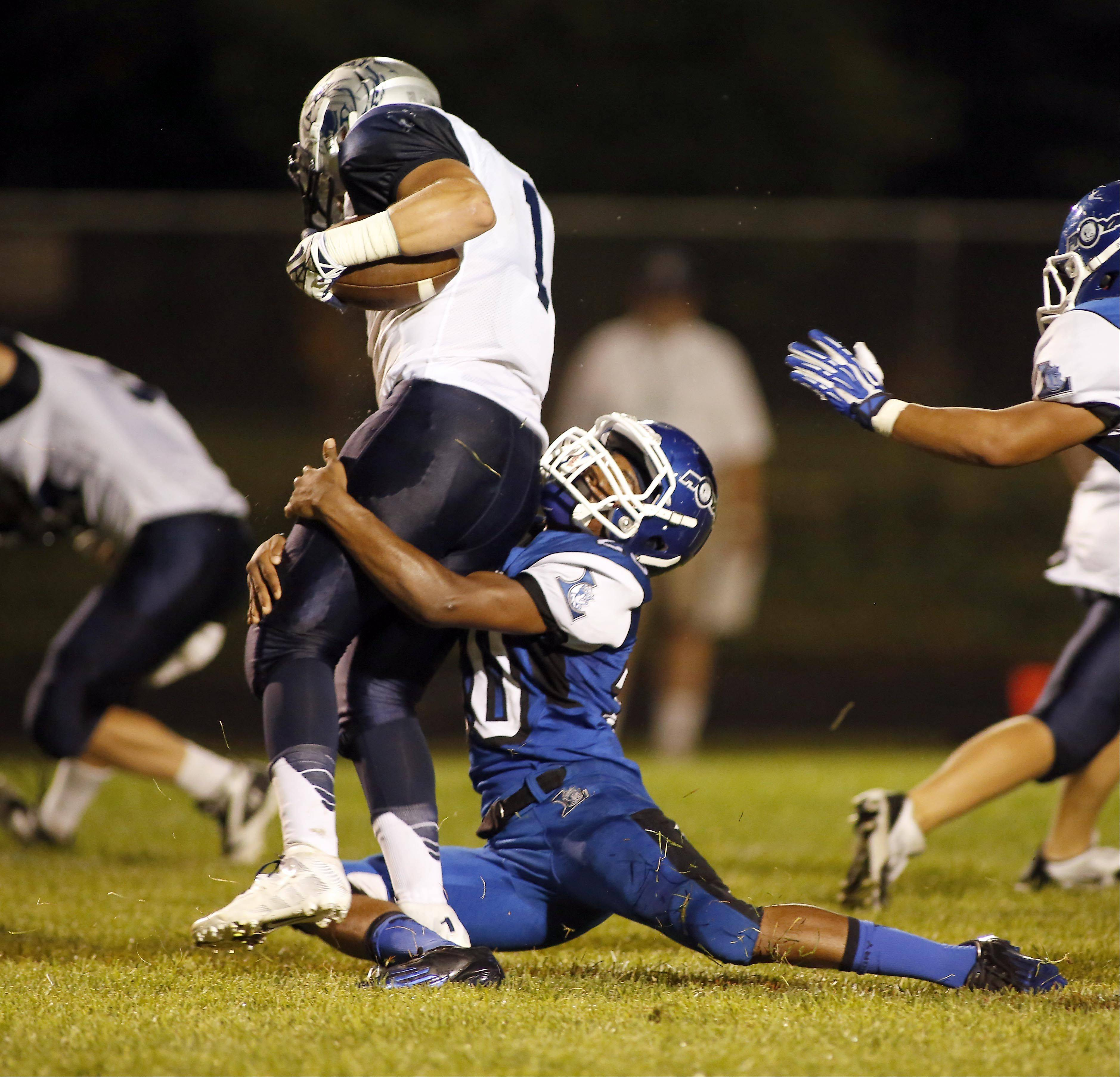 Larkin's Steffon Pruitt wraps up West Chicago's Danny Lazzerini at Memorial Field in Elgin Friday.