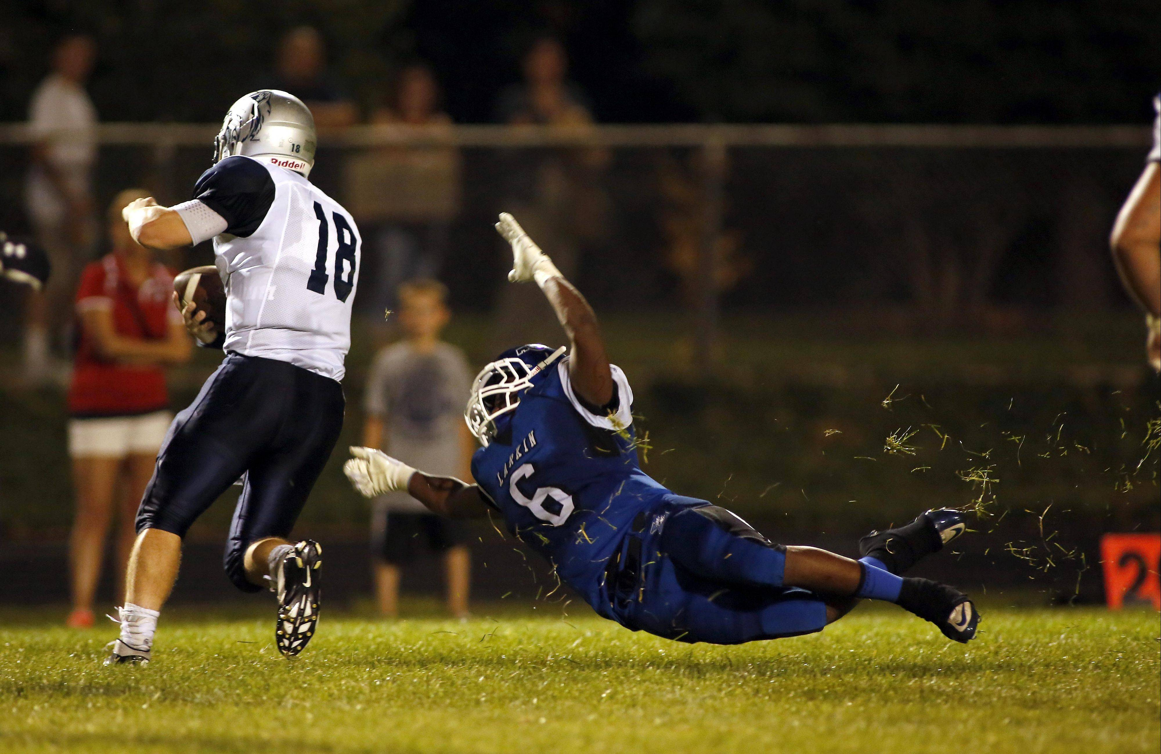 Larkin's Jeff Pruitt tries to bring down West Chicago's Jordan Lelito at Memorial Field in Elgin on Friday night.