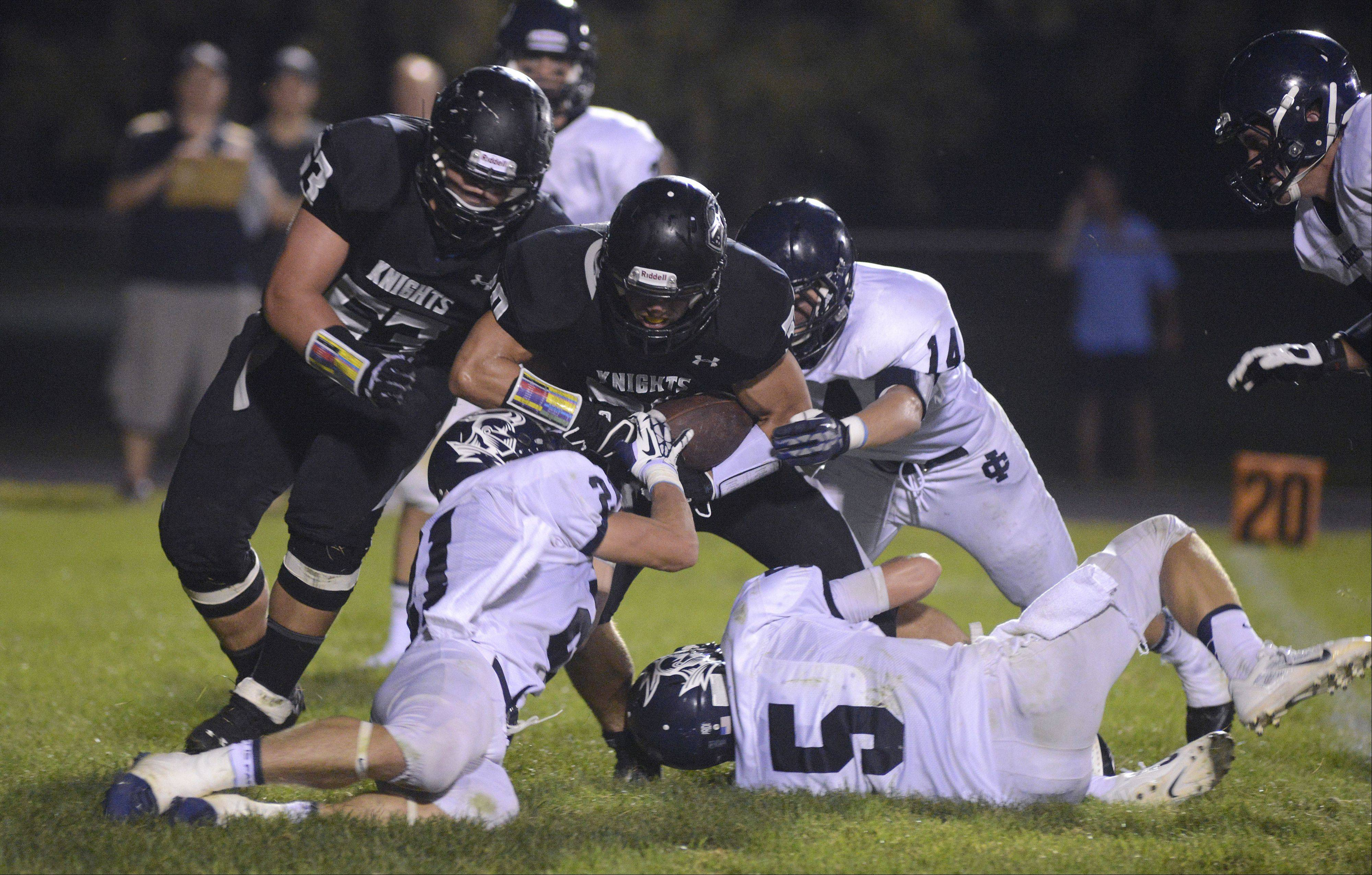 Kaneland's Jesse Balluff hunkers down with the ball while being tackled by IC Catholic Prep's James Janowski (21), Sean Sutton (5) and Max Eichhorn (14) in the first quarter on Friday, September 6.