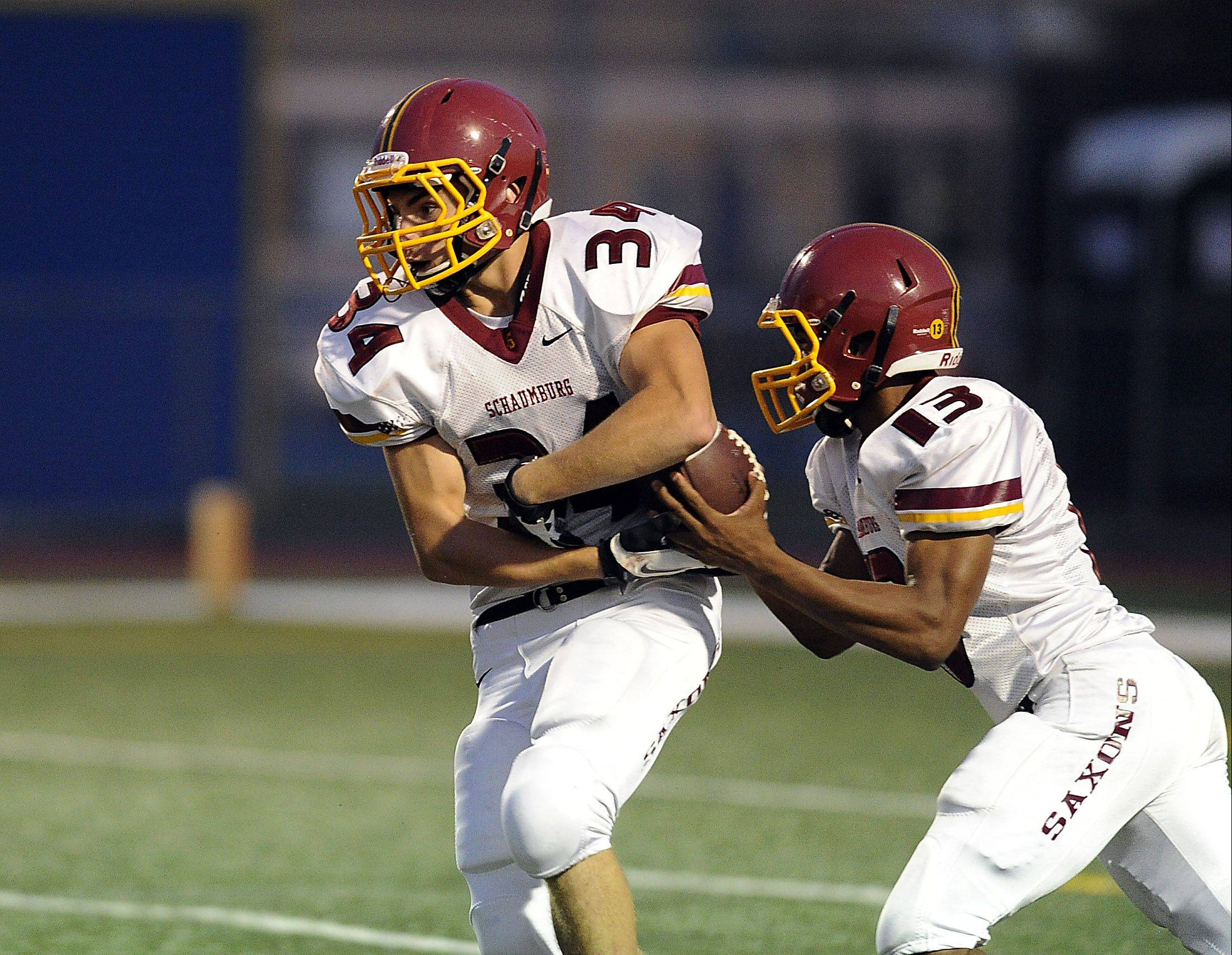 Schaumburg quarterback Stacey Smith fakes a handoff to Michael Jones before going for a touchdown Friday night at Wheeling.