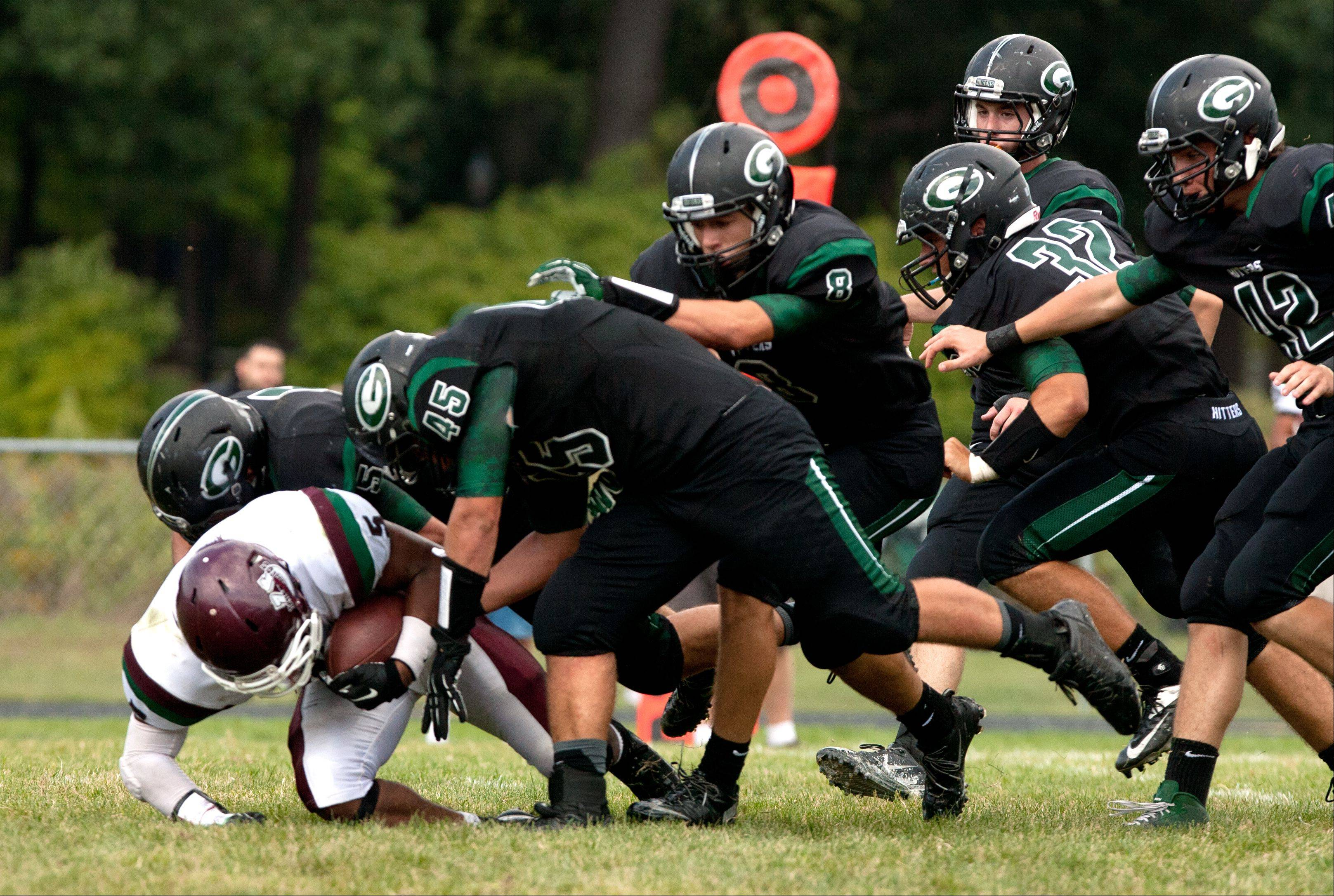 Glenbard West's defense swarms Morton's M. Hester, as the Hilltoppers build a 41-0 halftime lead.