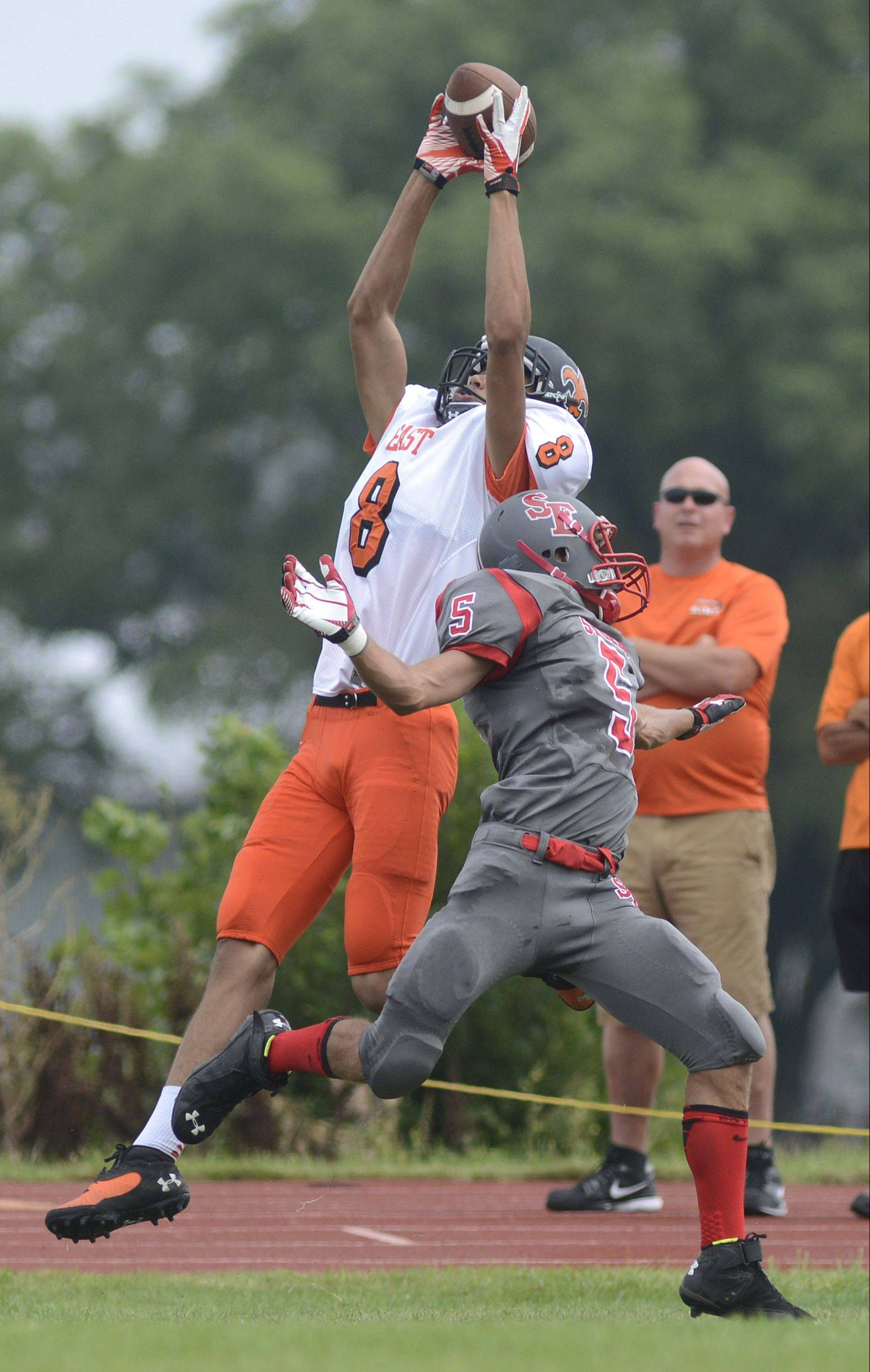 AJ Washington, pictured catching a touchdown in St. Charles East's season-opening win over South Elgin, is one of the basketball players making a big impact on the Saints' football team.
